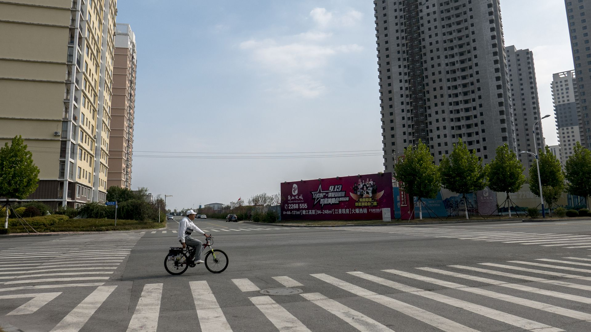 A man rides a bike through an empty city