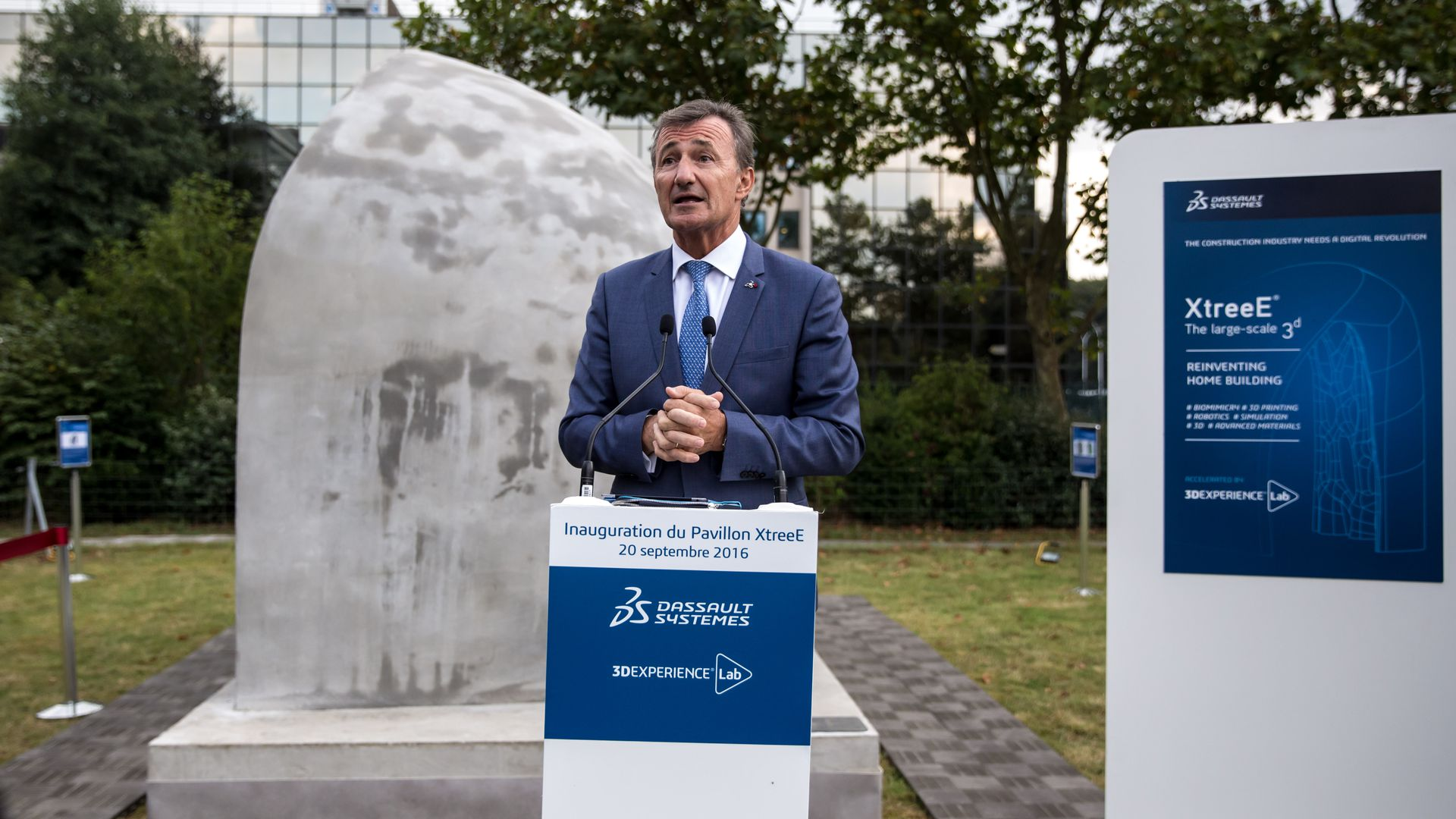 Dassault Systemes CEO Bernard Charles speaks behind a podium.