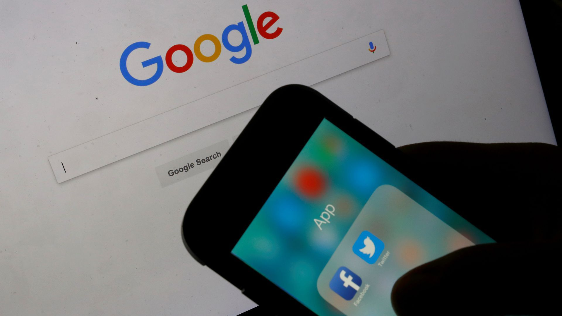 An iPhone showing Twitter and Facebook in front of a Google search page