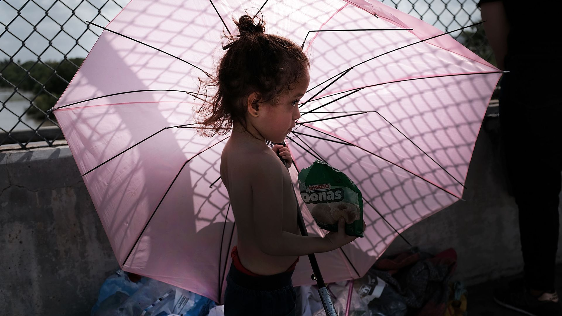 A child migrant holding a bag of chips and a big, pink umbrella