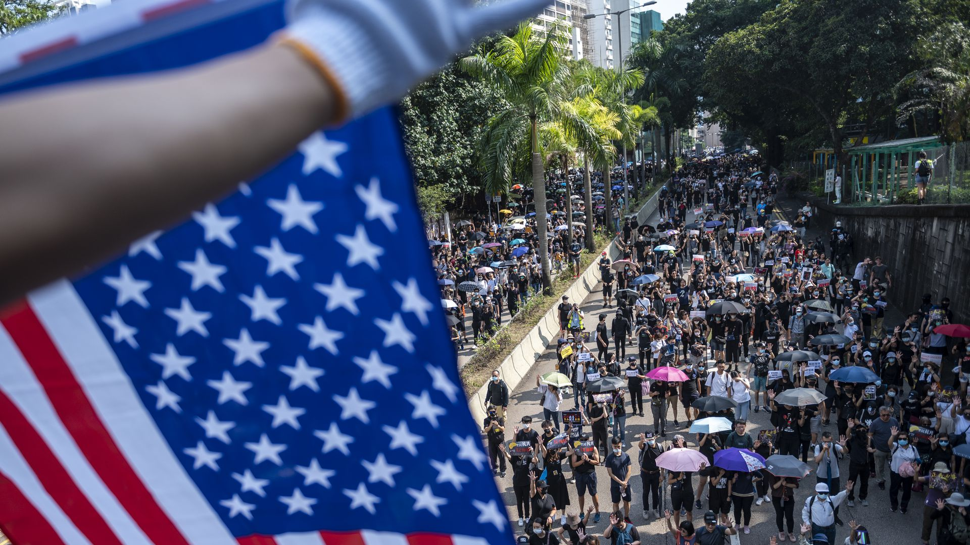 A Protester is seen holding up a US Flag above other protester during an Anti-Government Protest in Tsim Sha Tsui district in Hong Kong, China, October 20
