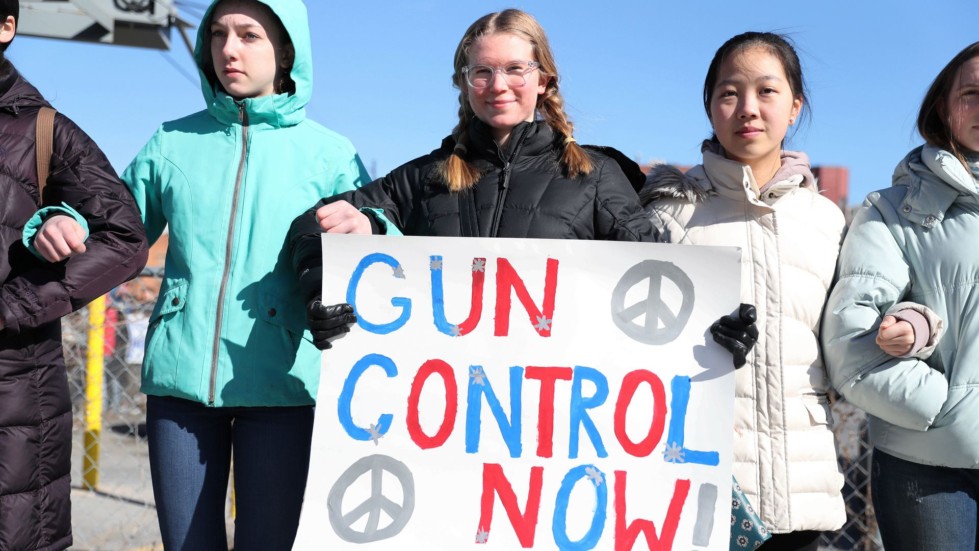 "girls hold sign that says ""gun control now!"""