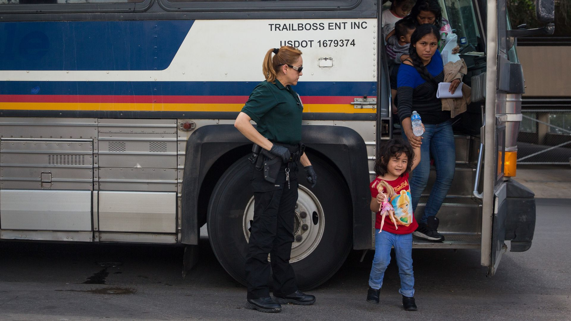 In this image, a young girl steps off a bus with her mother holding her hand while carrying another child. A guard watches.