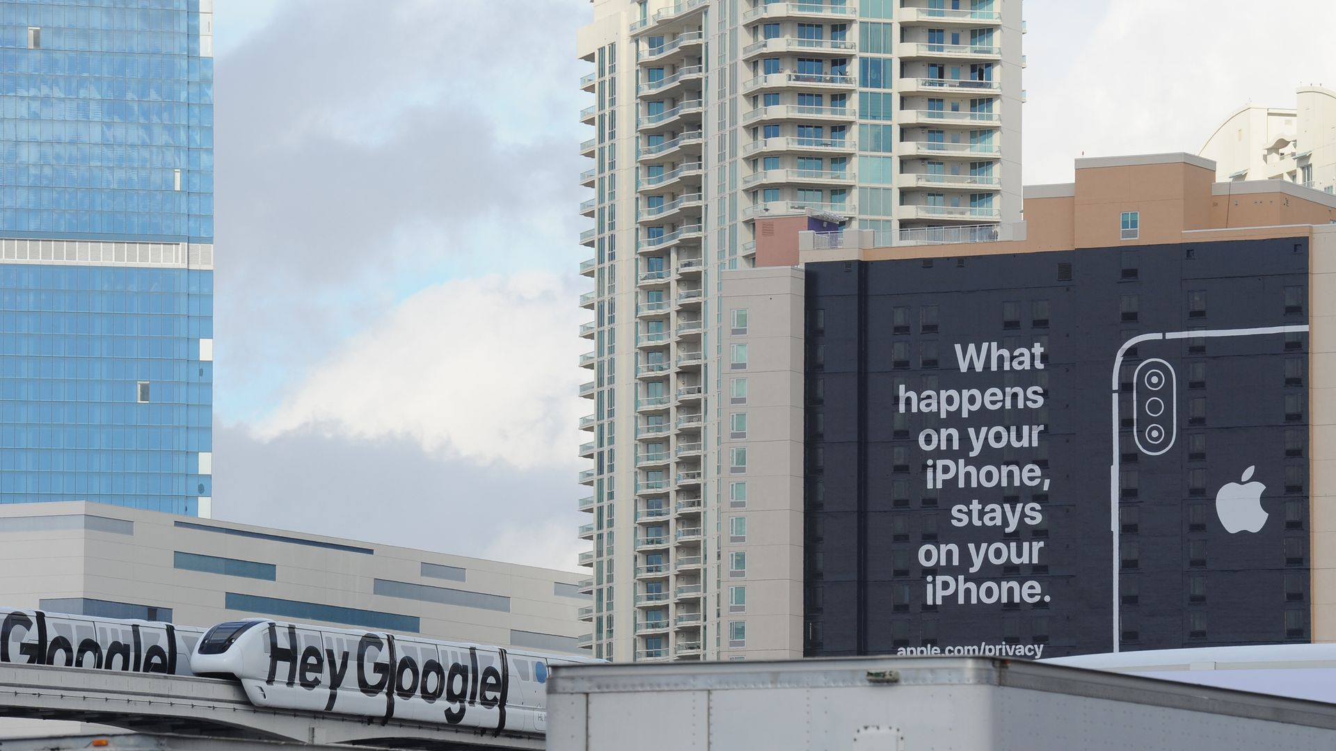"An ad that says ""What happens on your iPhone, stays on your iPhone"" next to a monorail that says ""Hey Google"""