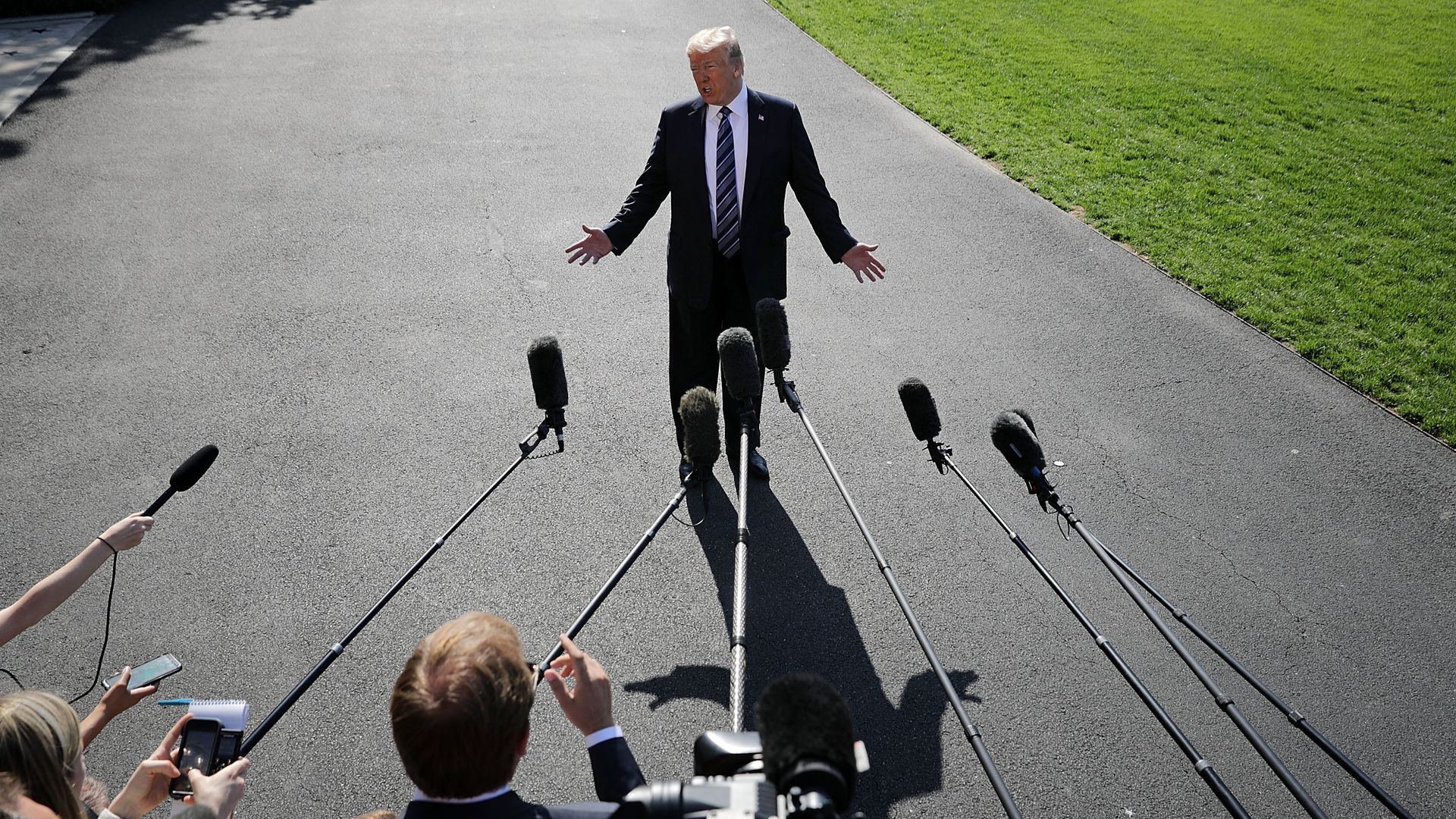 Donald Trump standing on asphalt surrounded by microphones.