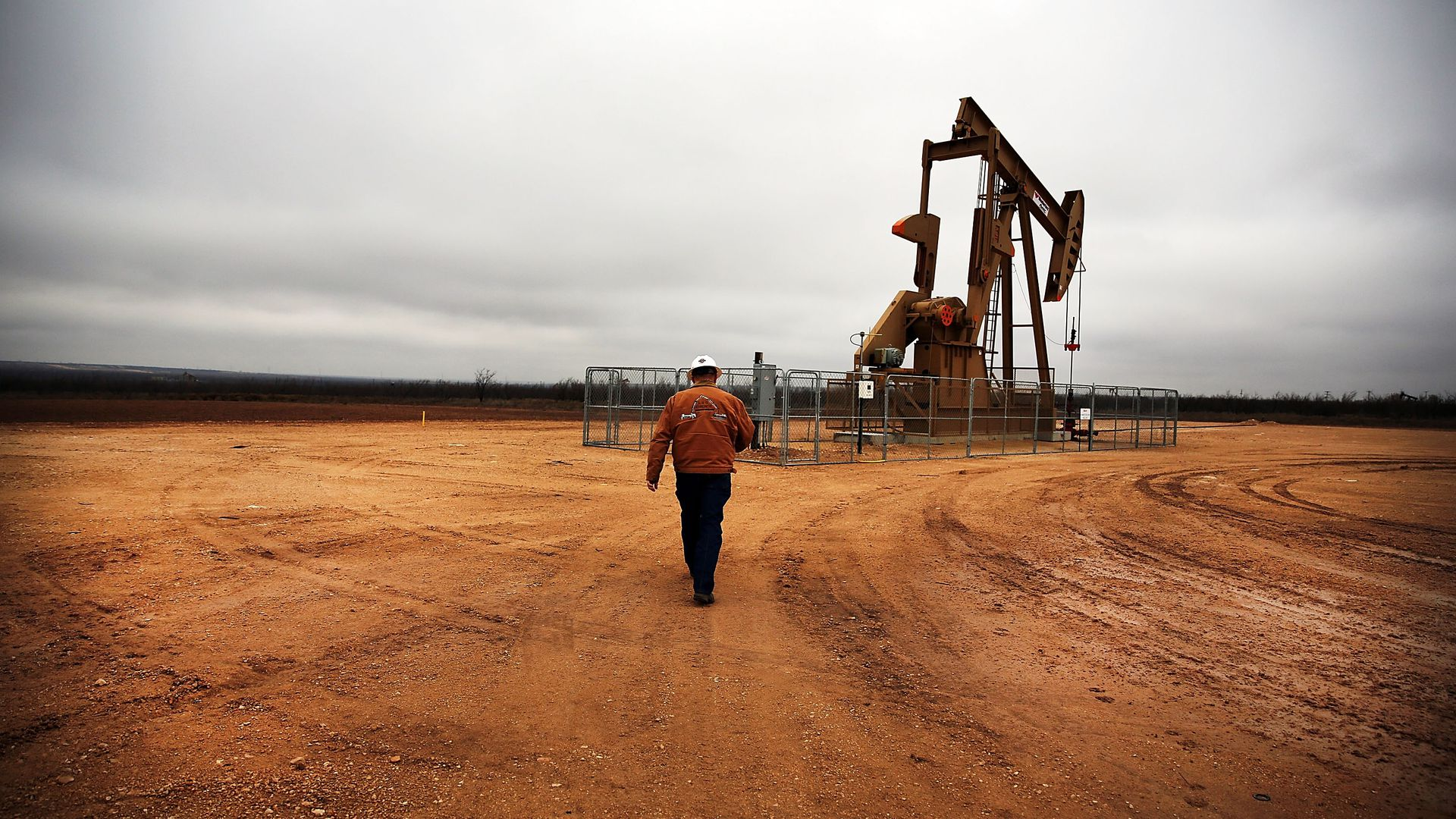 A man walks towards an oil well alone.
