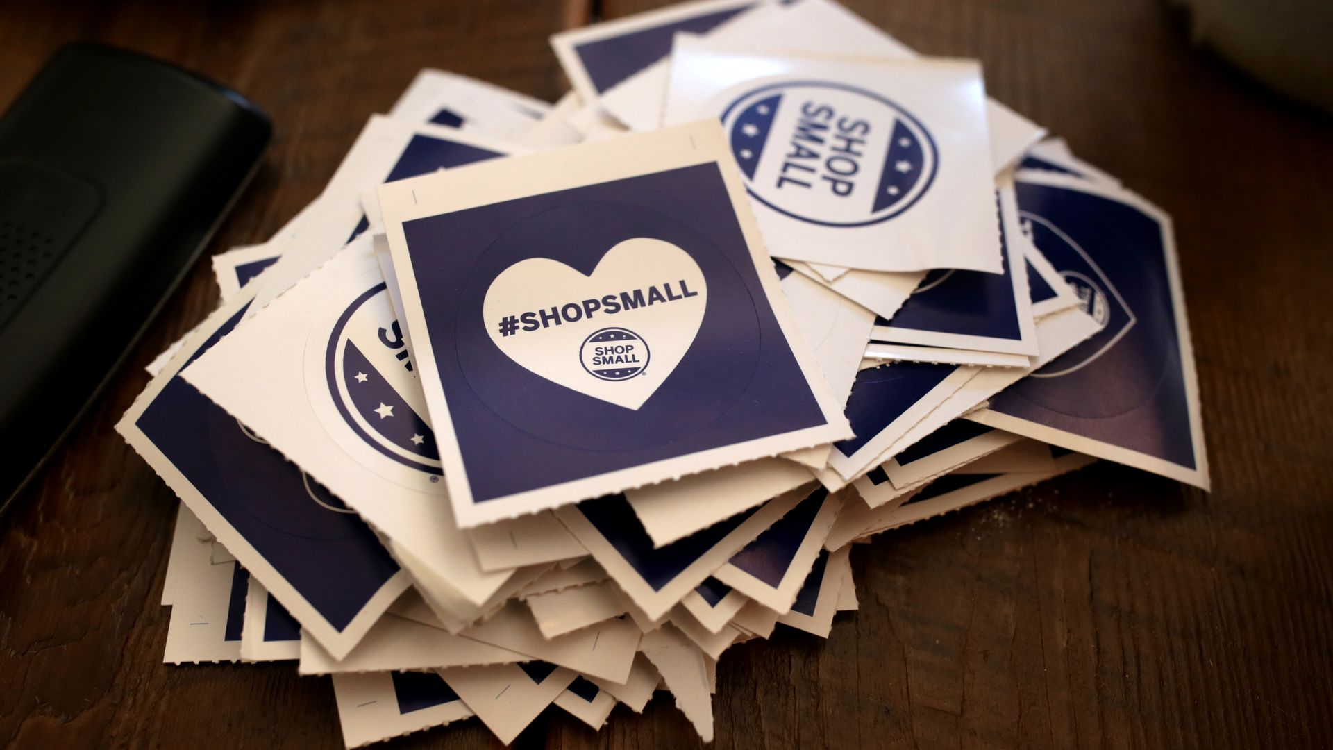 "A stack of stickers that read: ""Shop Small."""