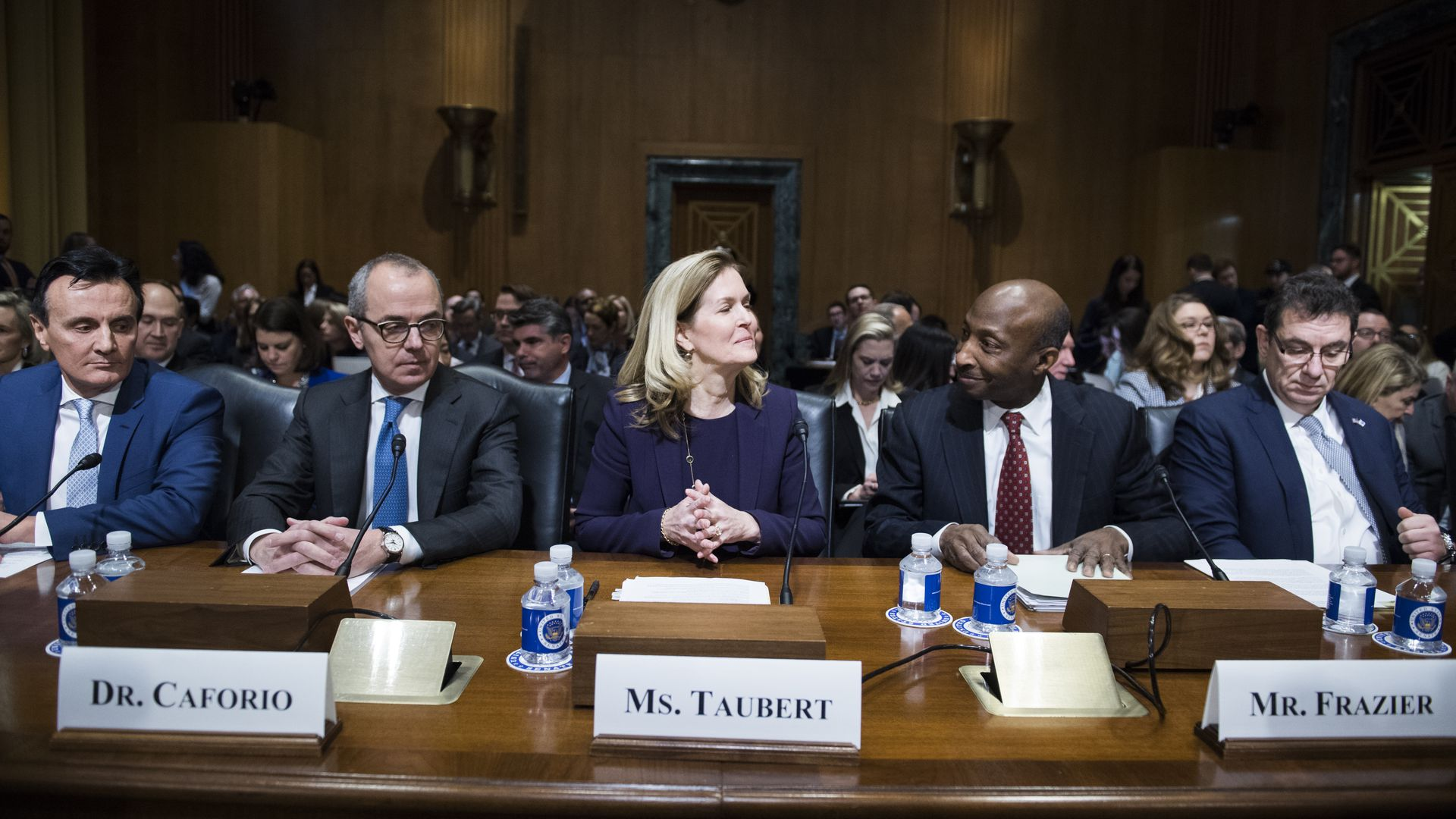 Pharmaceutical executives sit behind a table during U.S. Senate testimony.