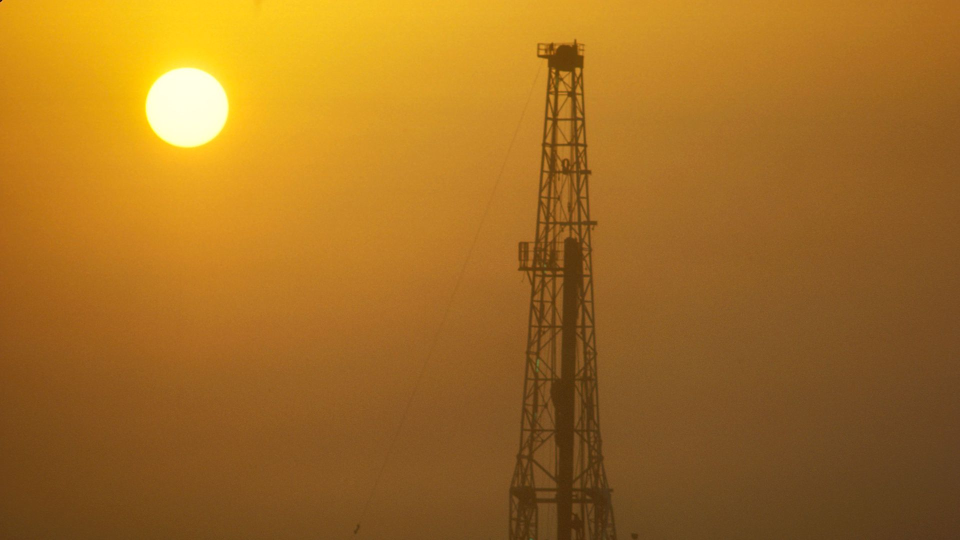 Photo of sun setting on an onshore oil rig