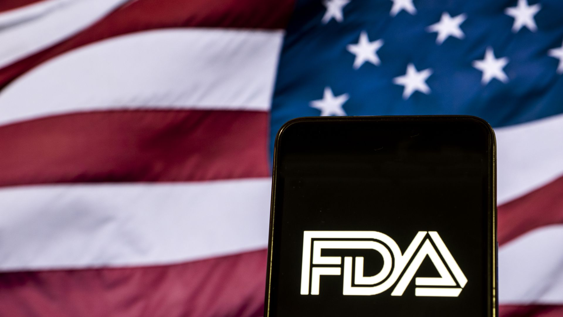 A phone holds up the FDA logo, an American flag waves in the background.