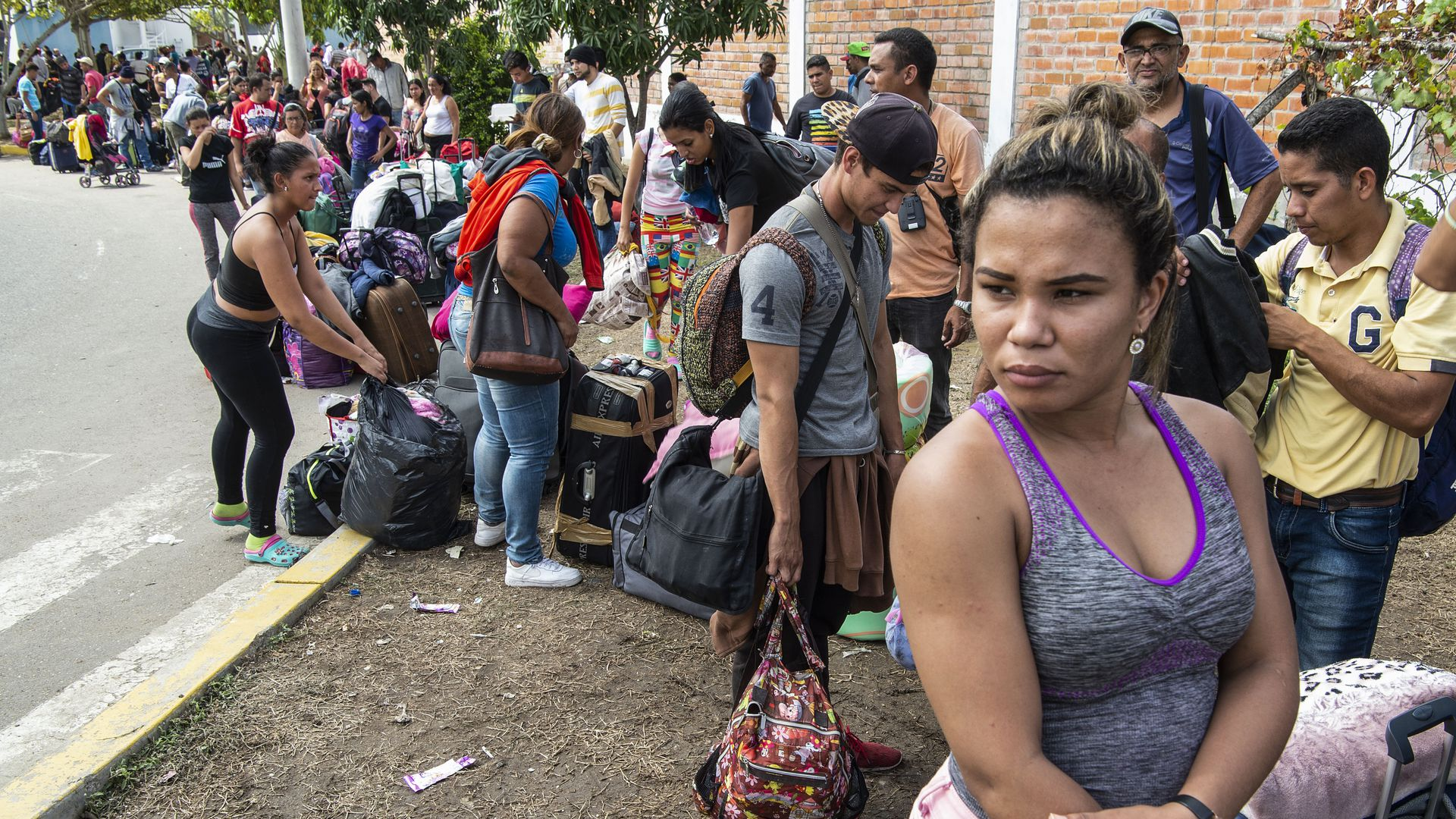 Venezuelan migrants lined up with their bags