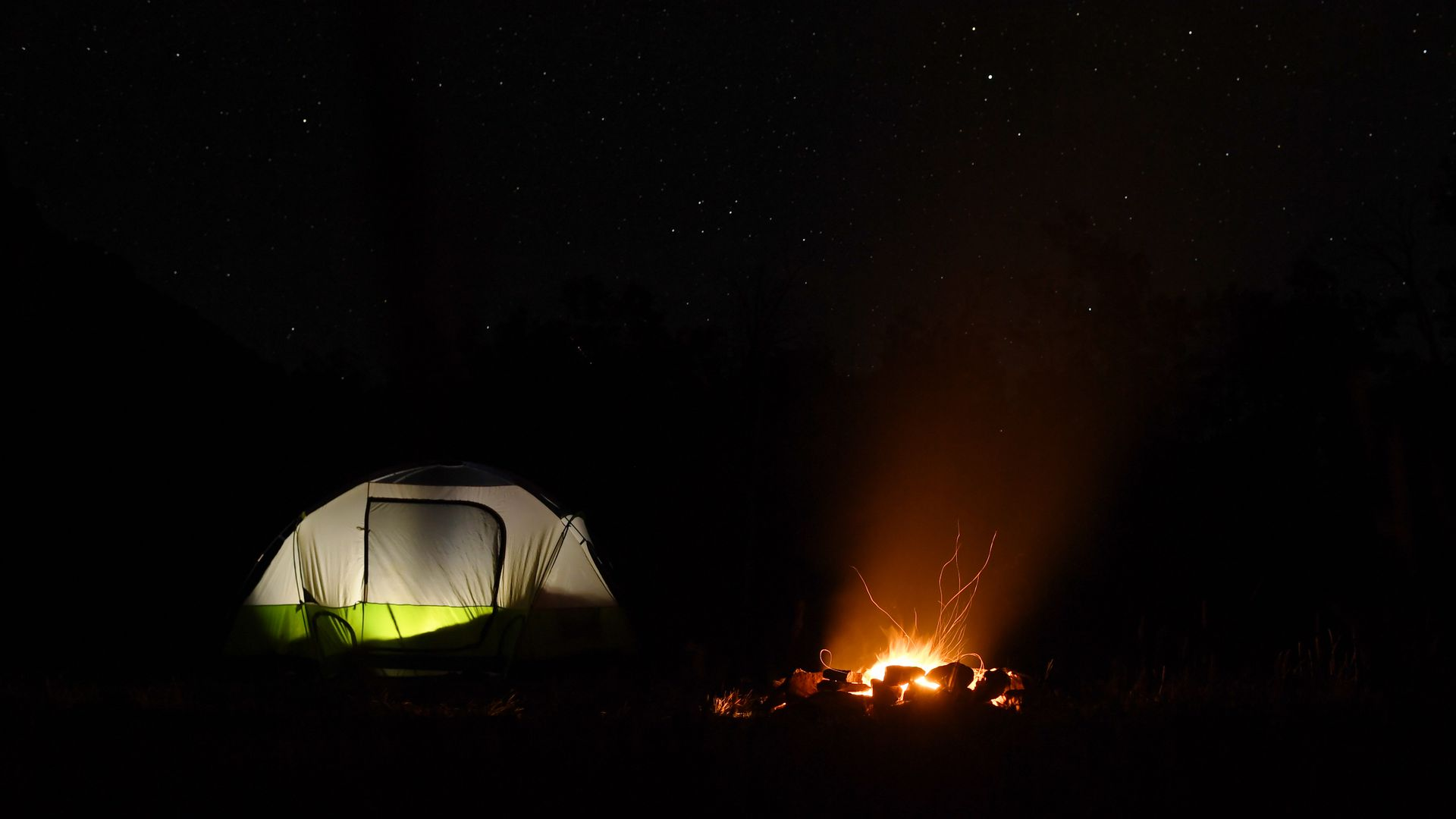 A campfire glows in a fire ring with campers in a tent nearby on Kebler Pass outside of Crested Butte.
