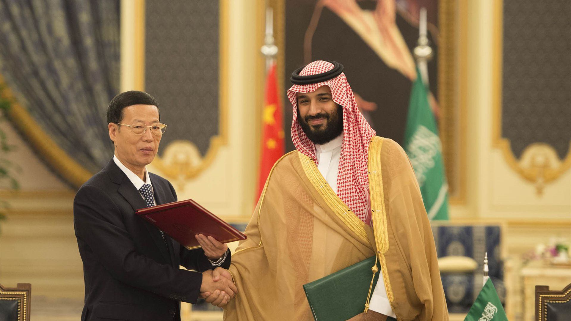 In this image, Saudi Crown Prince Mohammed bin Salman shakes hands with a Chinese diplomat in front of the Chinese and Saudi Arabian flags.