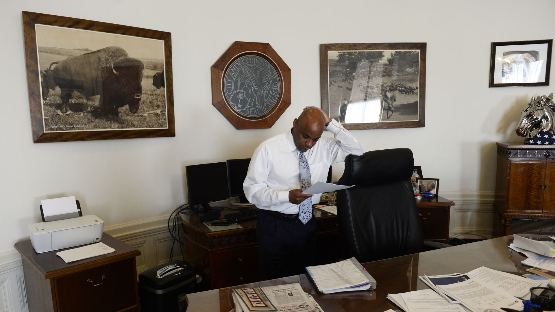 A photo of Denver Mayor Michael Hancock standing at his desk and looking down at some documents with his hand on his head.