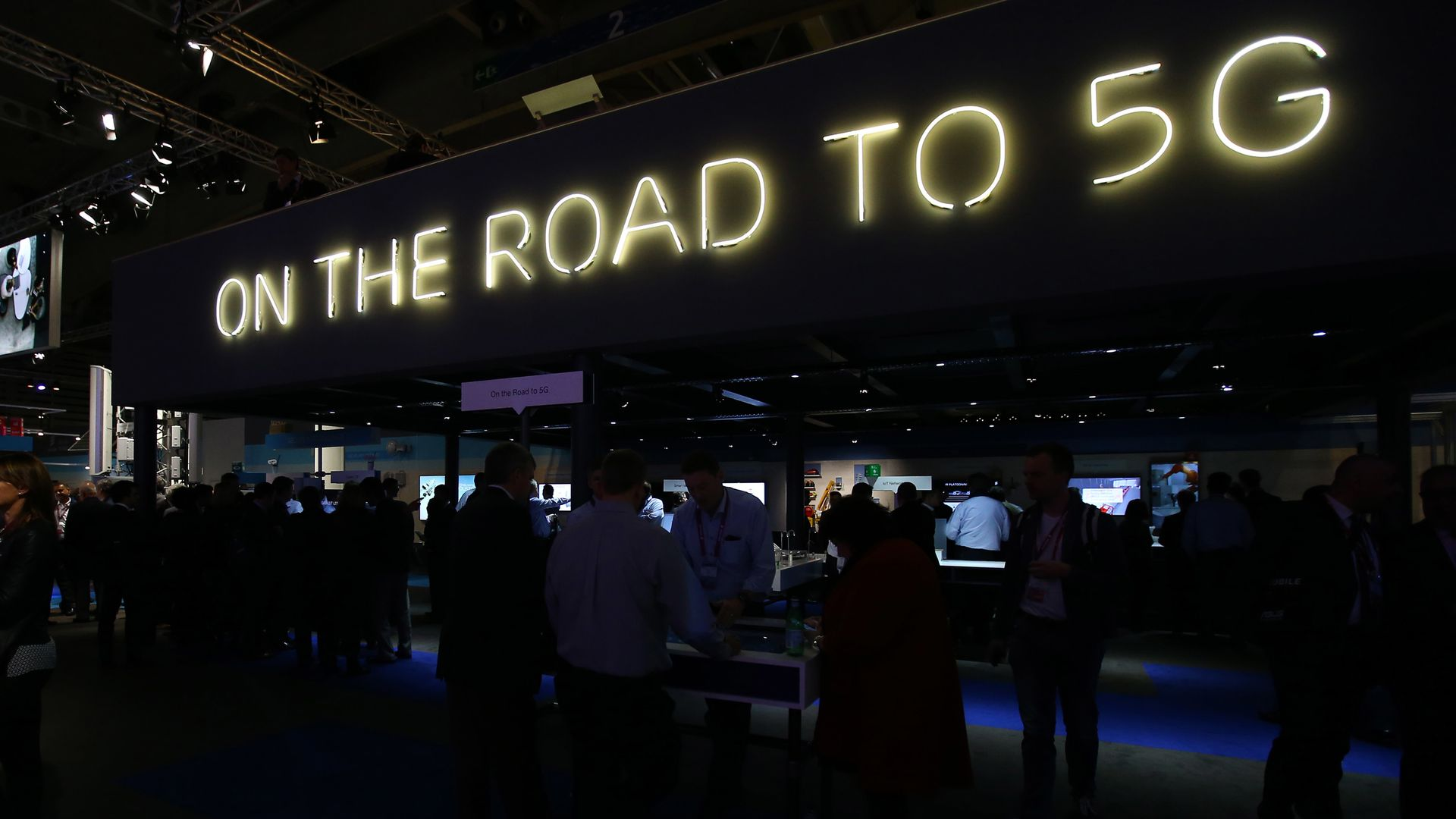 "A neon sign at a conference reads ""On The Road To 5G"""