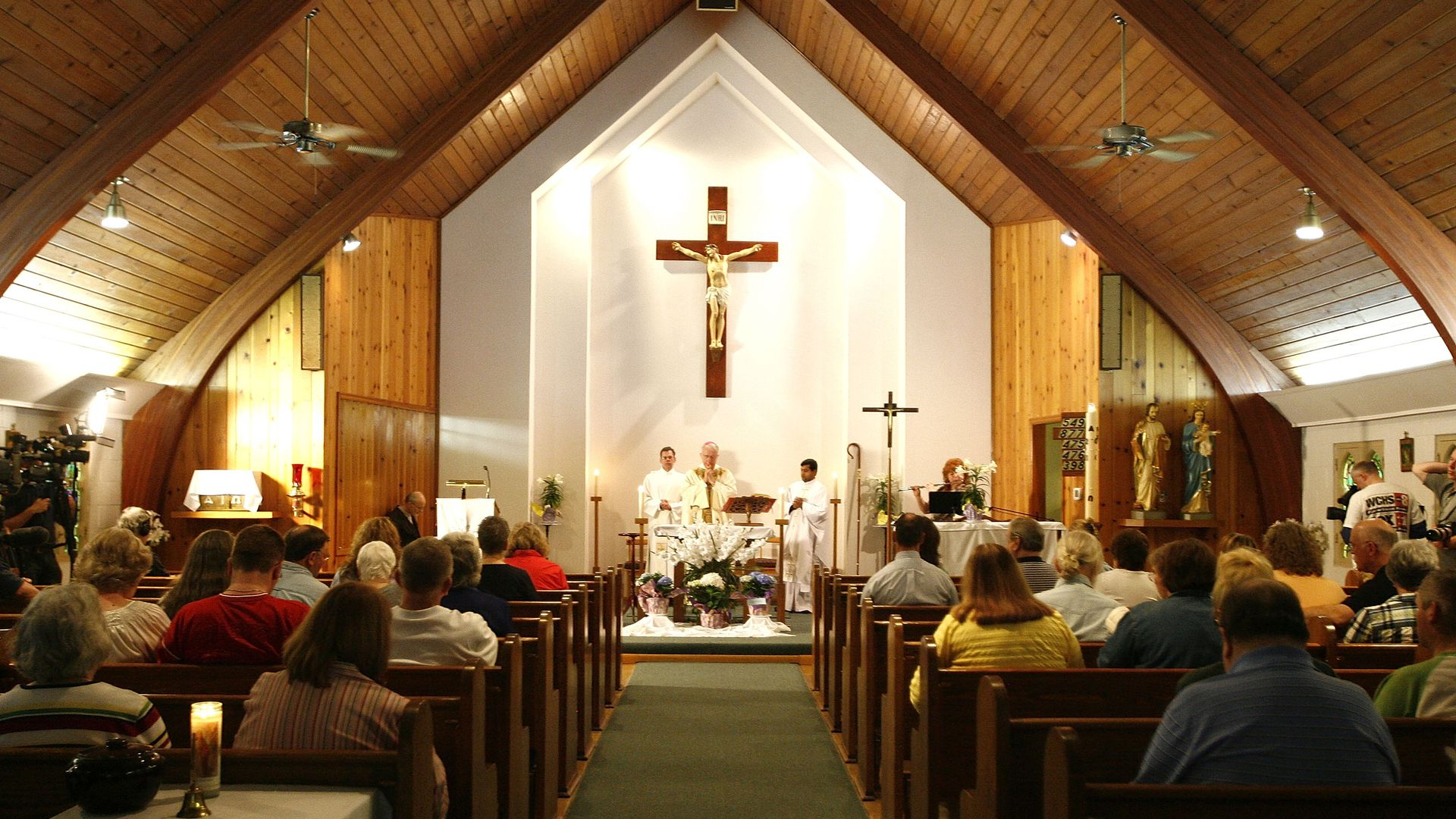 In this image, two rows of pews in a church are packed as church goers face a sermon being held in front of a white wall.