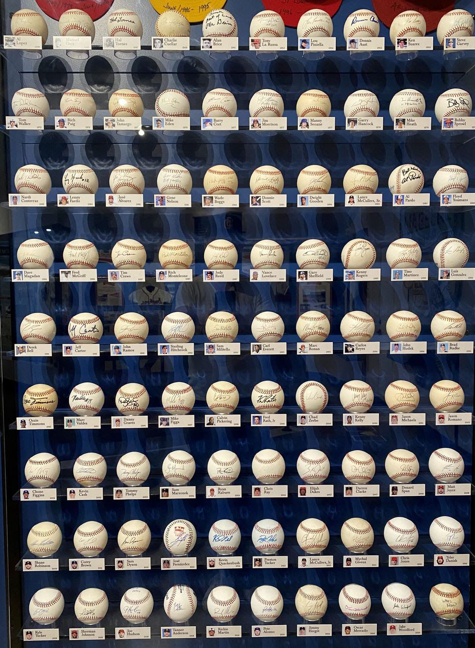 A glass display full of autographed baseballs.