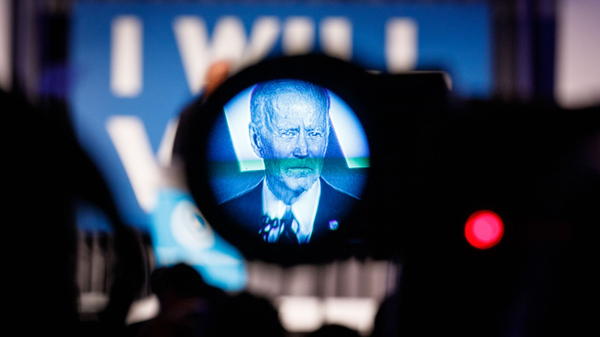 In this image, Biden is seen in a blue filter on a TV camera as he's being filmed while speaking on stage.