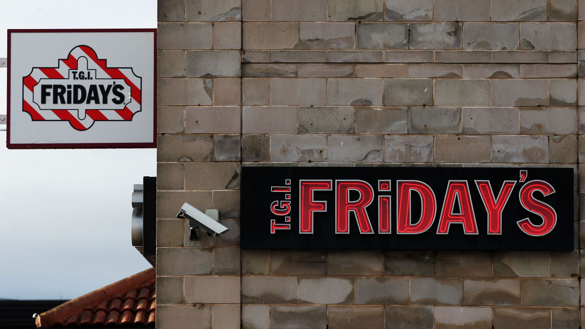 A surveillance camera next to a T.G.I. Friday's sign