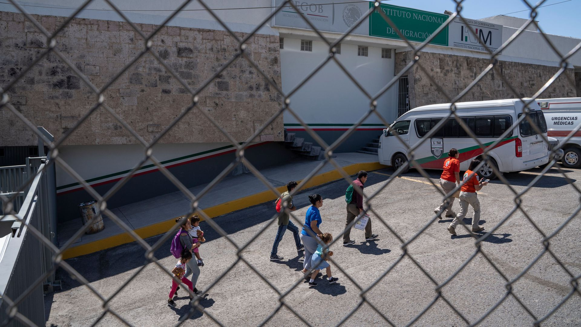 Migrants are led out of the National Institue of Migration in downtown Ciudad Juarez, Mexico. Seen through a chain link fence.