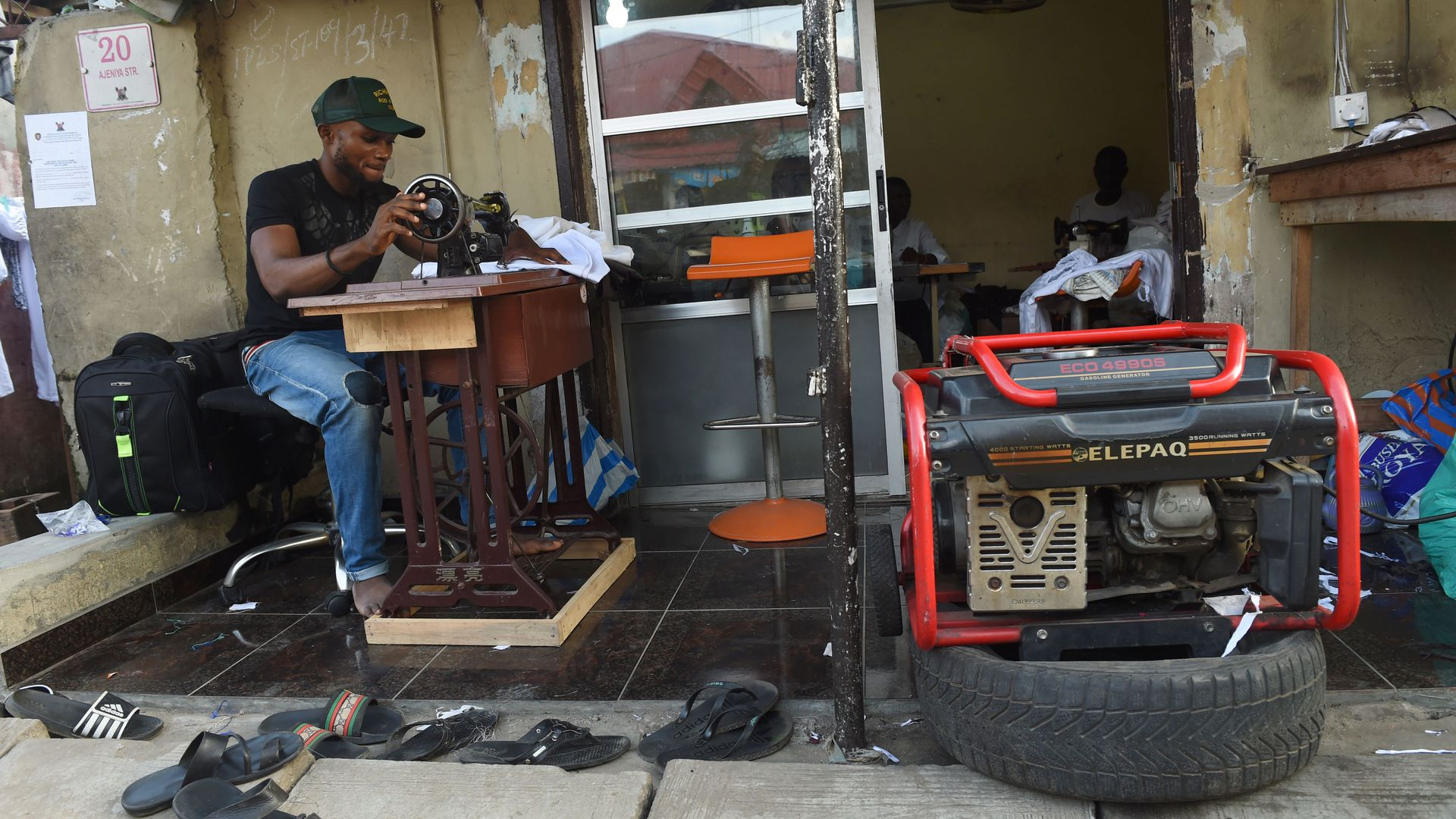 A tailor uses a generator for power due to the epileptic public power supply in Lagos on September 27, 2016.