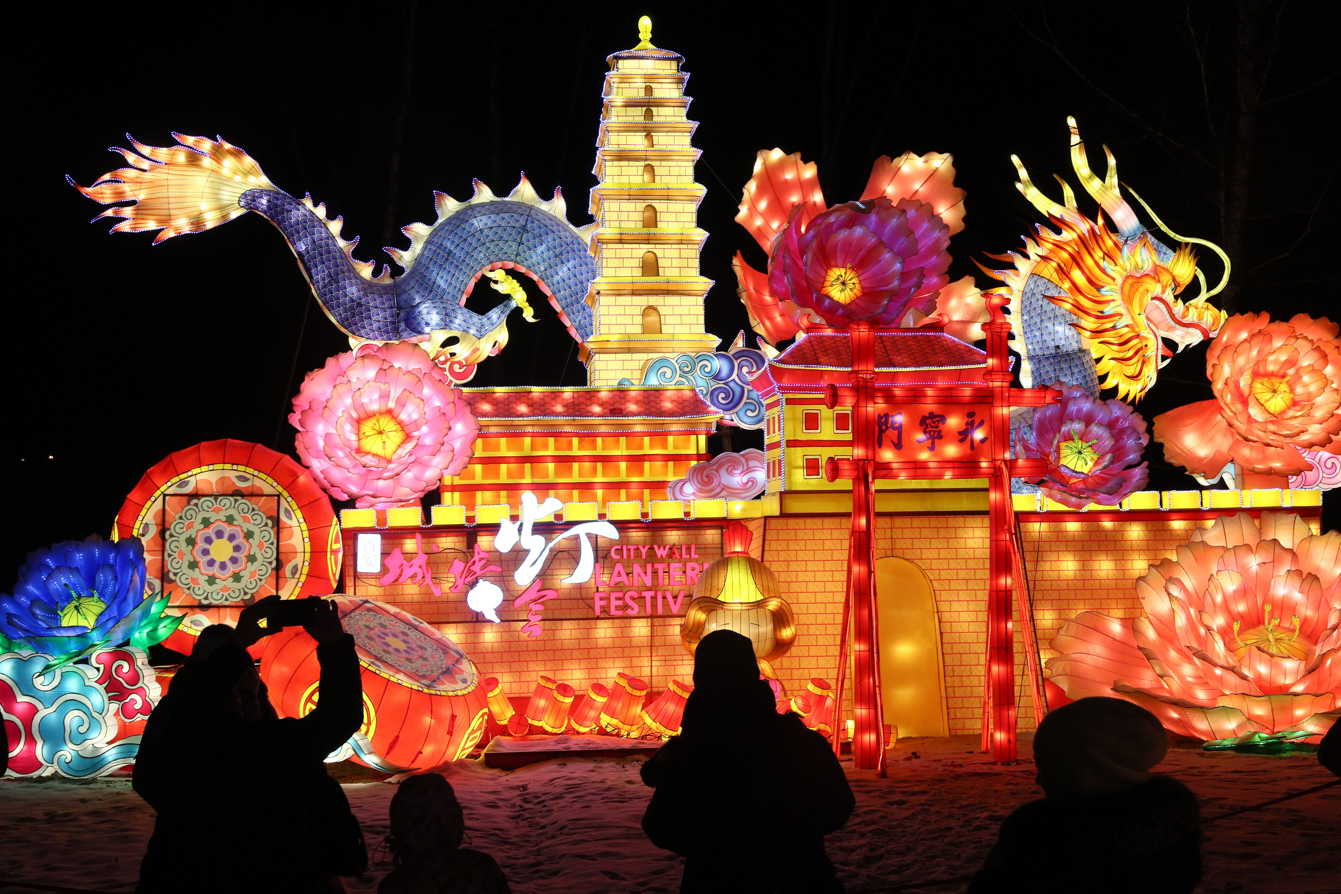 In this image, a gigantic lit-up dragon and wall is seen