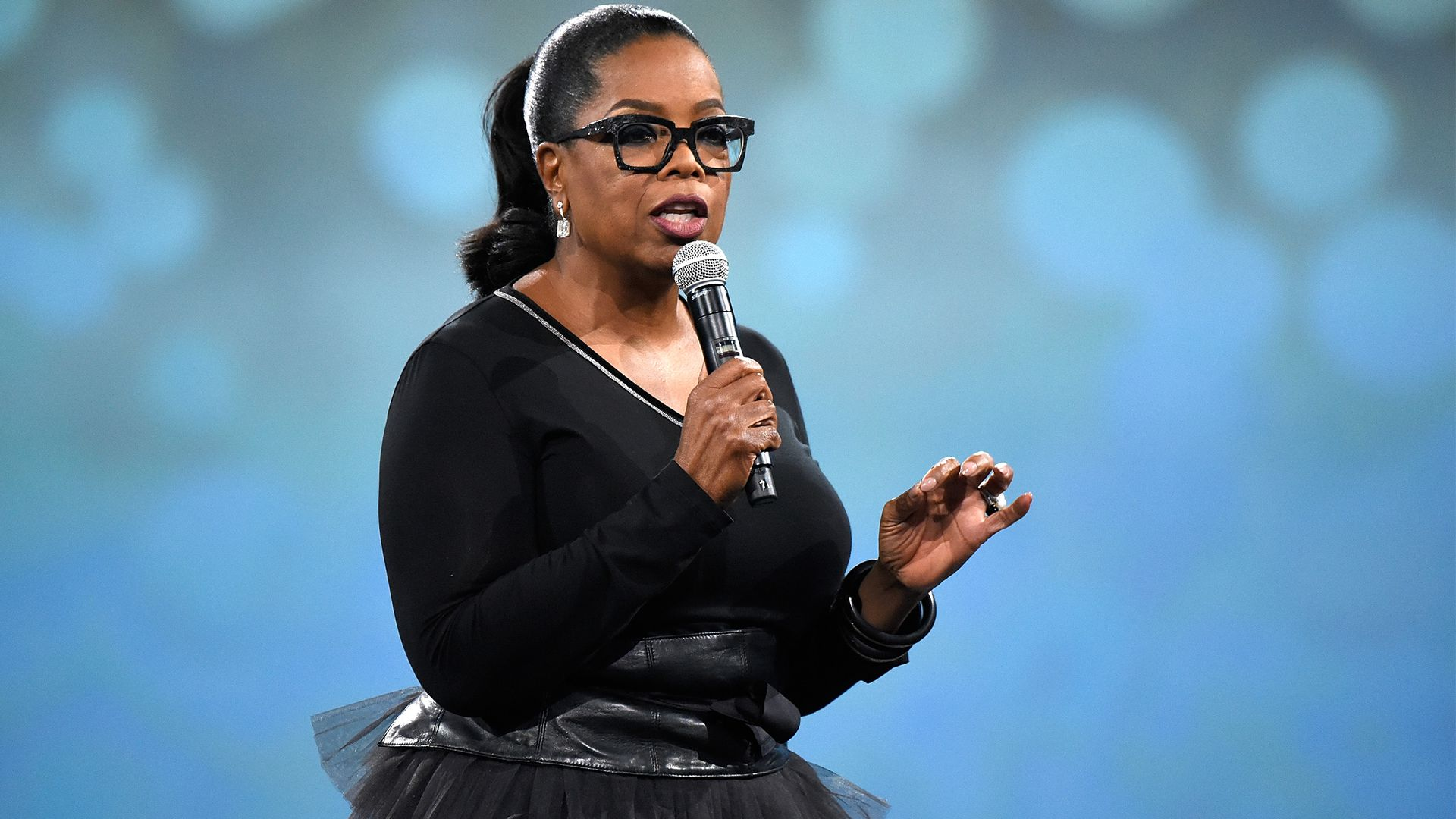 Oprah Winfrey. Wearing black outfit holding microphone.