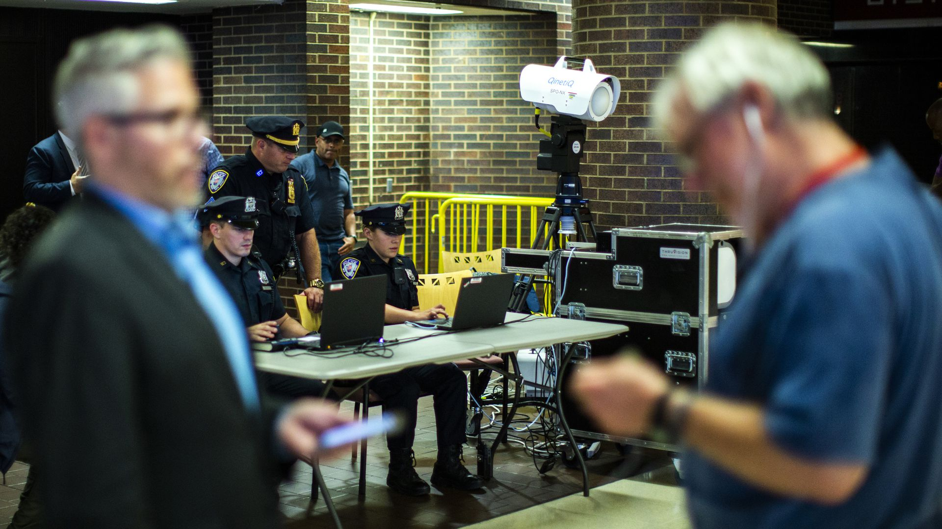 Two men walk by a table as police test body scanning equipment.