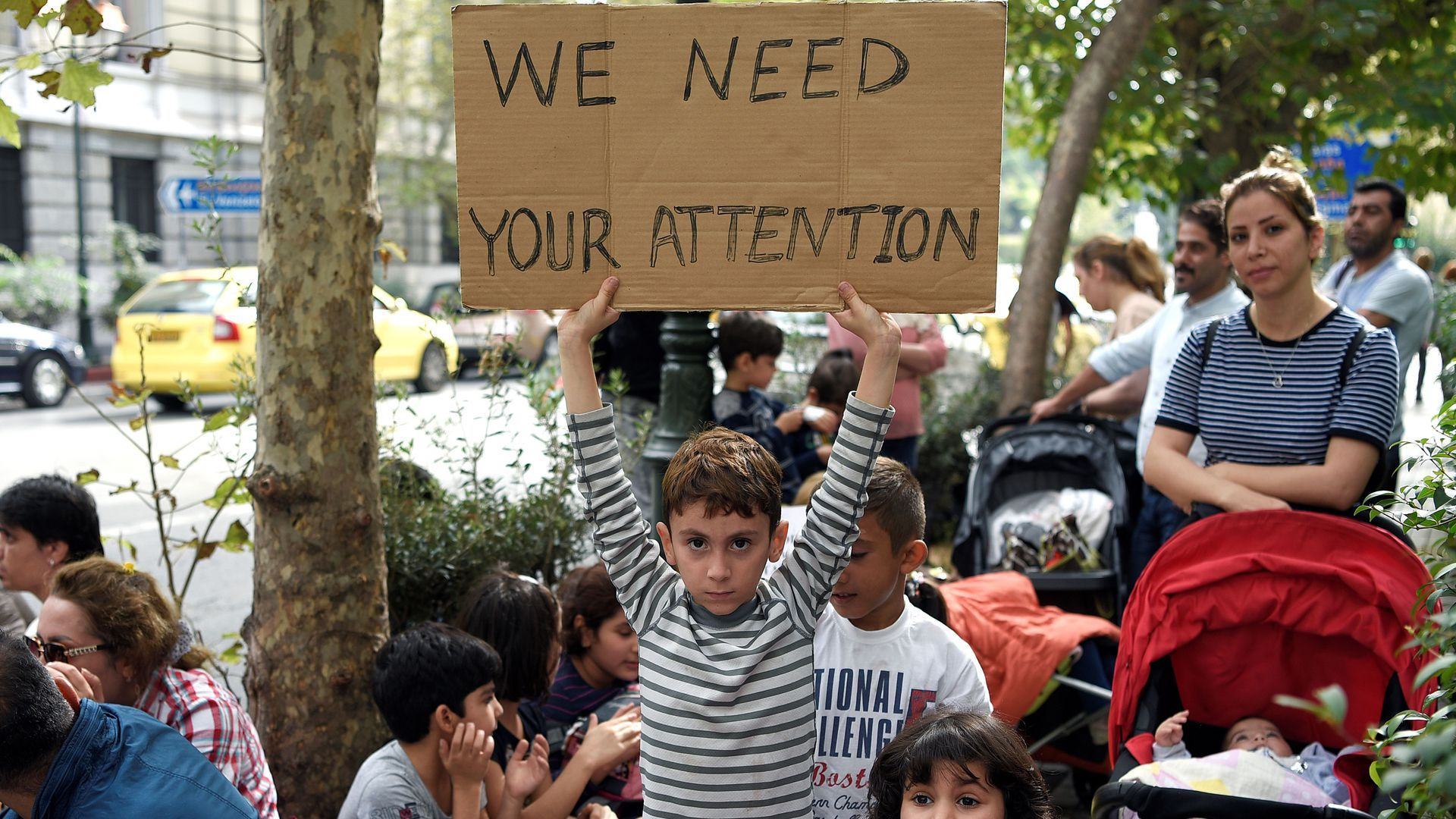 "A young boy holds a sign that reads, ""We need your attention"""