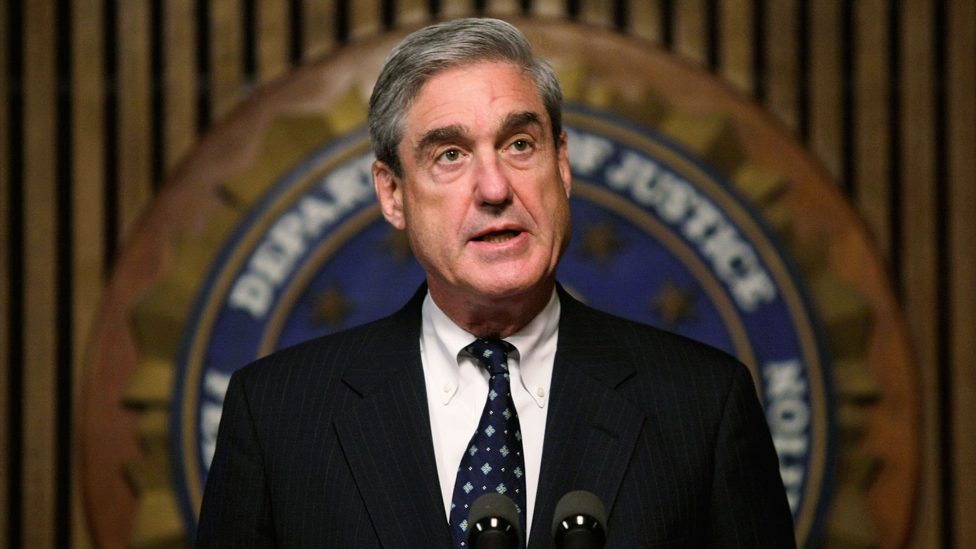 In this image, a suited Robert Mueller stands in front of a microphone podium with the logo of the Department of Justice behind him.