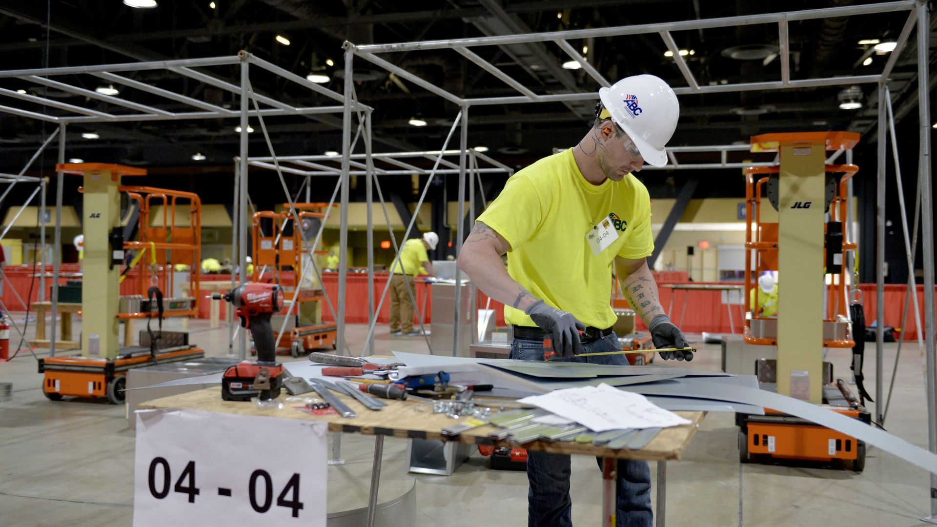 In this image, a man in a bright T-shirt and a white hard hat works over a table in a warehouse.