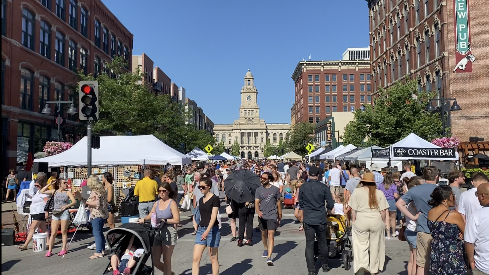 A crowd of people walking outside at the Downtown Des Moines Farmers Market.