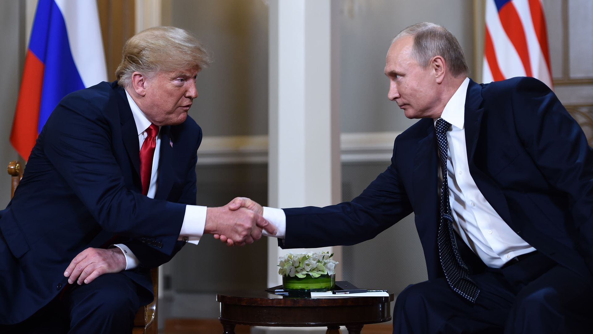 Donald Trump and Vladimir Putin shake hands.