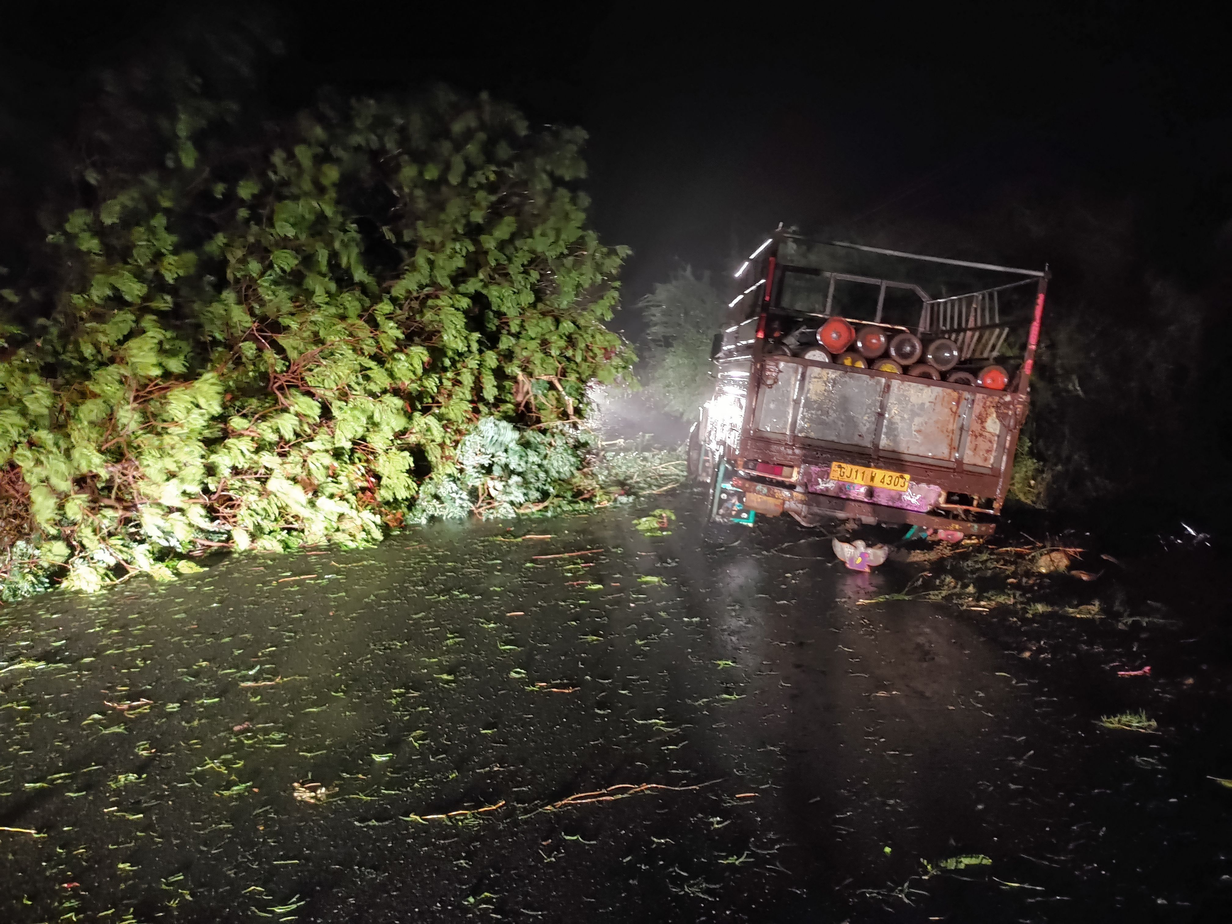 A picture taken on May 17, 2021 shows a truck loaded with oxygen cylinders stuck as trees fell due to impact of approaching Cyclone Tauktae, near Mahuva, in Gujarat state, western India.
