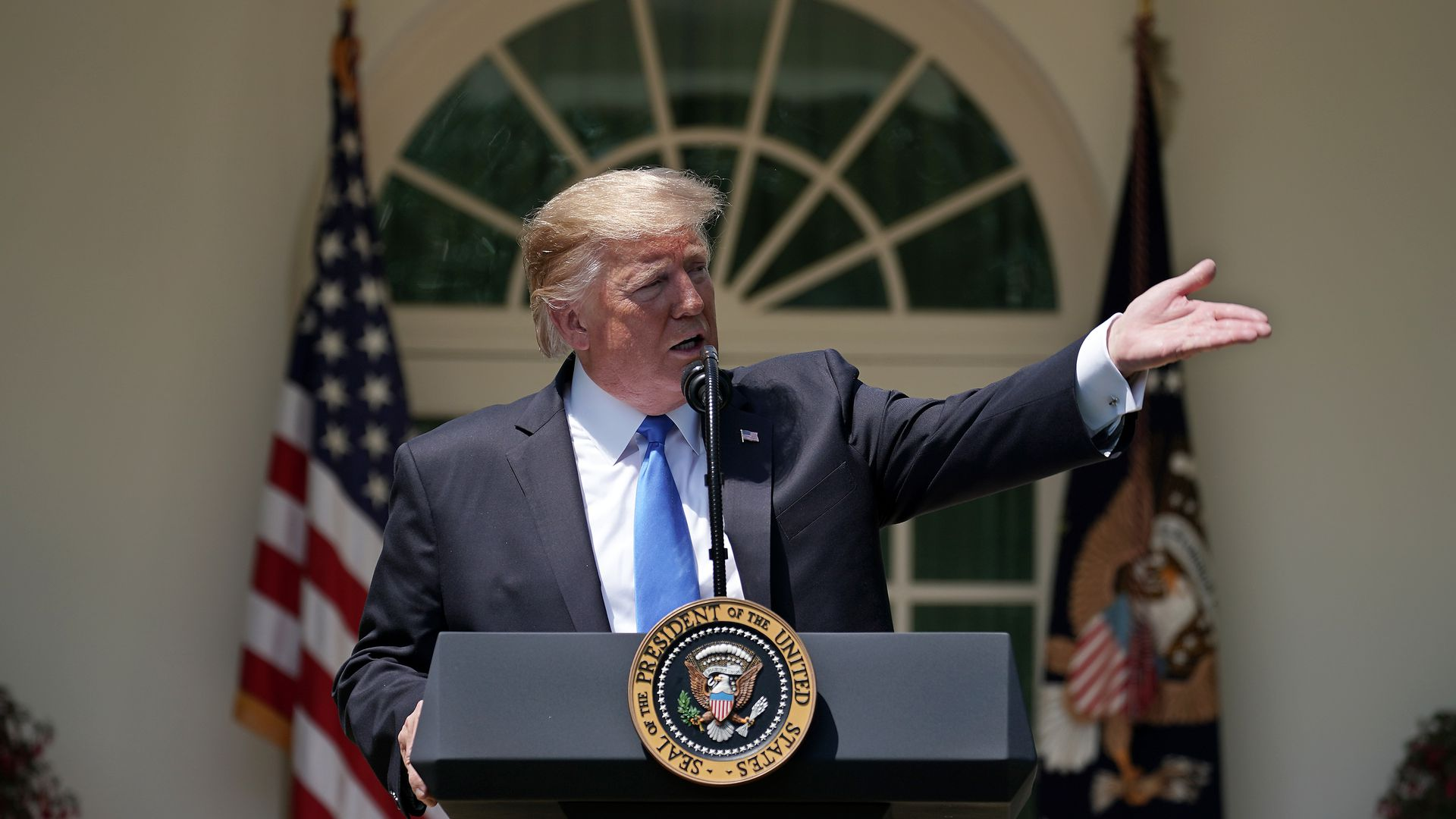 In this image, Trump gestures to the right while standing behind a podium.