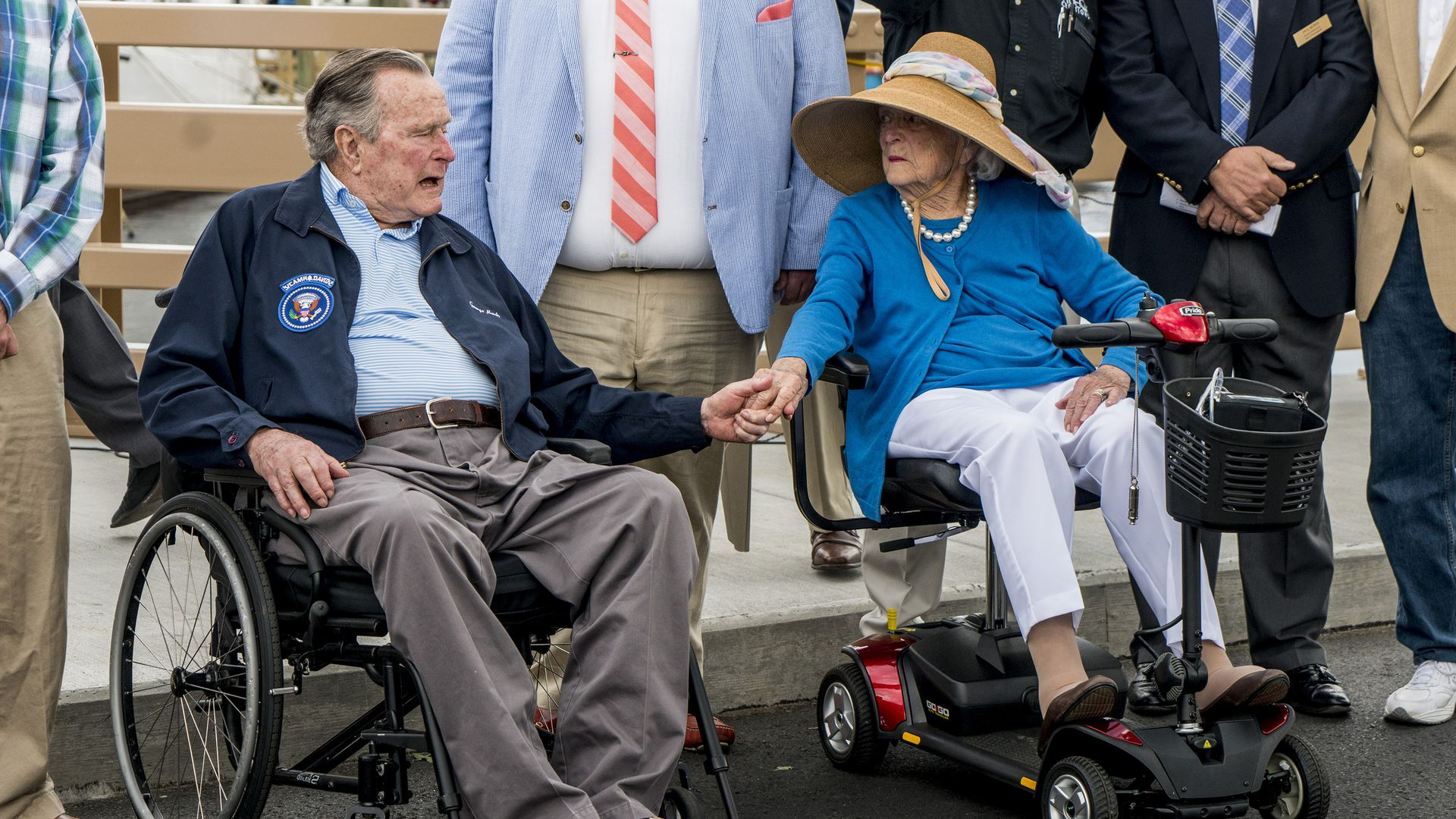 Former President George H.W. Bush and first lady Barbara Bush hold hands and talk.