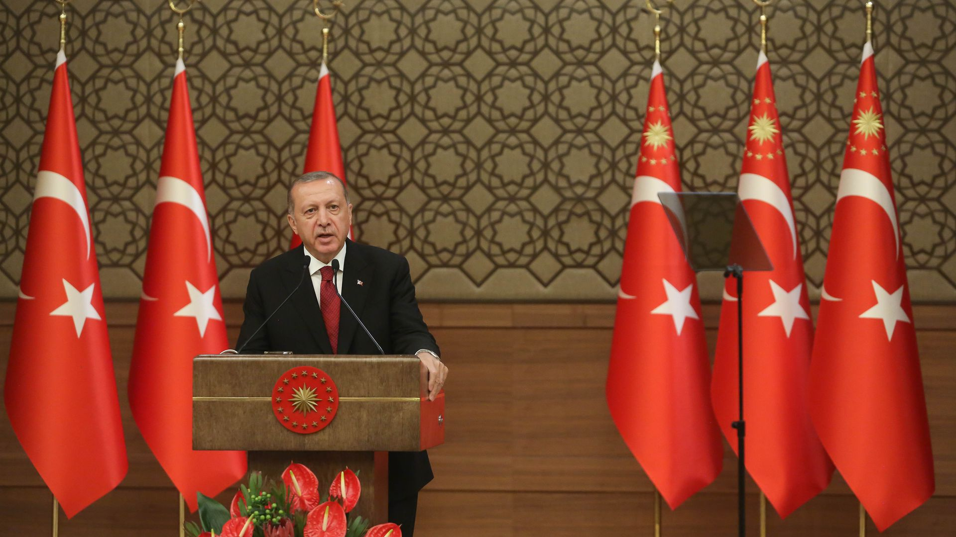 Turkey's President Erdogan giving a speech in front of Turkish flags.