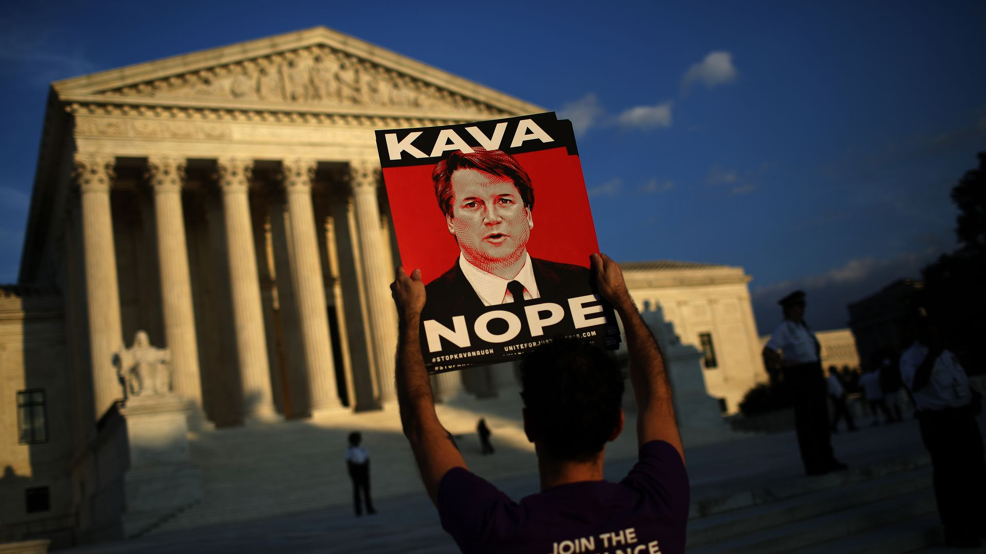 A protestor stands before the Supreme Court.