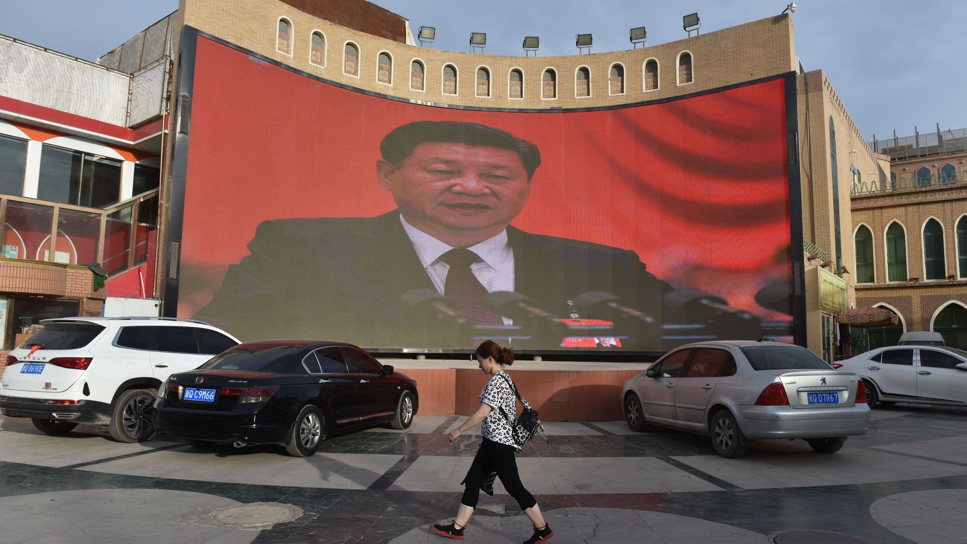 This photo taken on June 4, 2019 shows people walking past a screen showing images of Chinese President Xi Jinping in Kashgar, in China's western Xinjiang region.