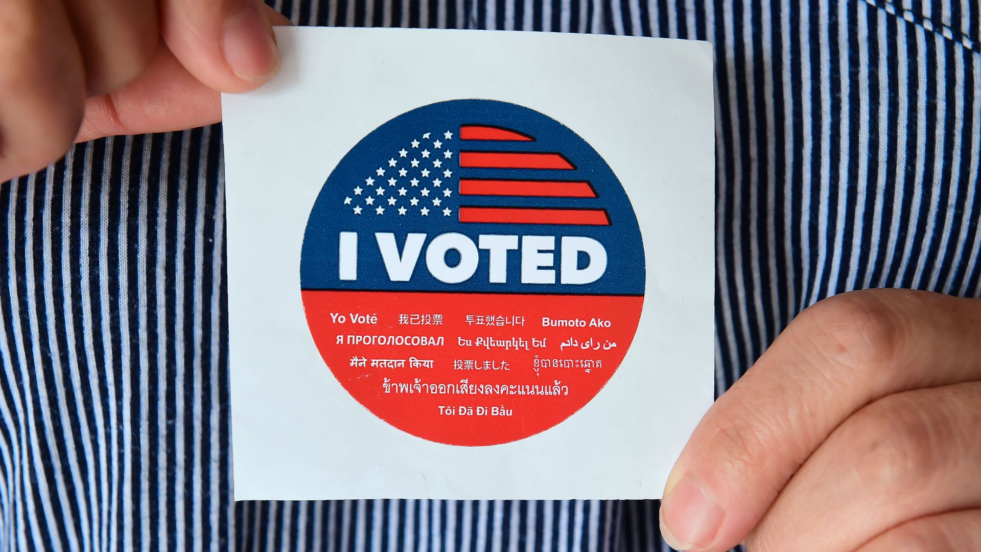 "Fingers hold an ""I voted"" sticker."