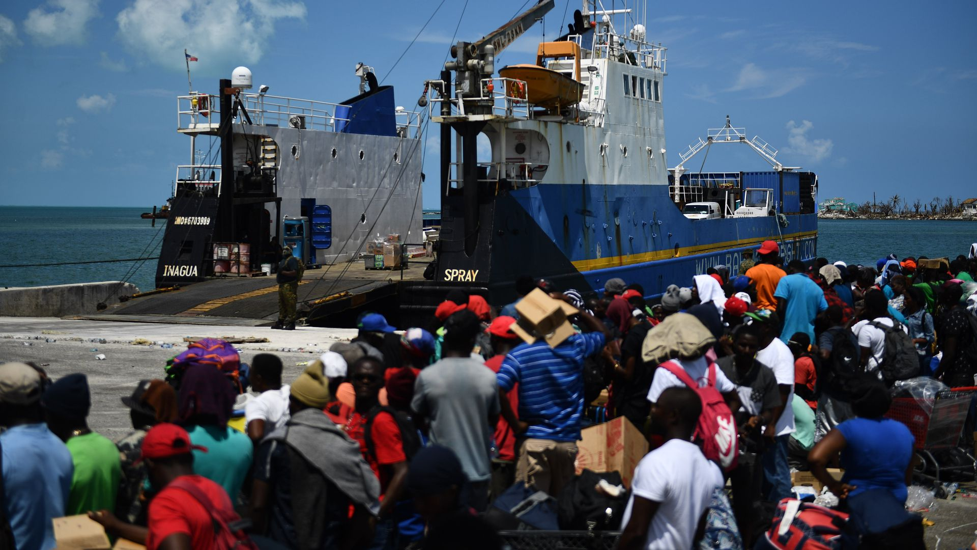 People wait to board a cargo ship for evacuation to Nassau at the port after Hurricane Dorian September 7, 2019, in Marsh Harbor, Great Abaco.