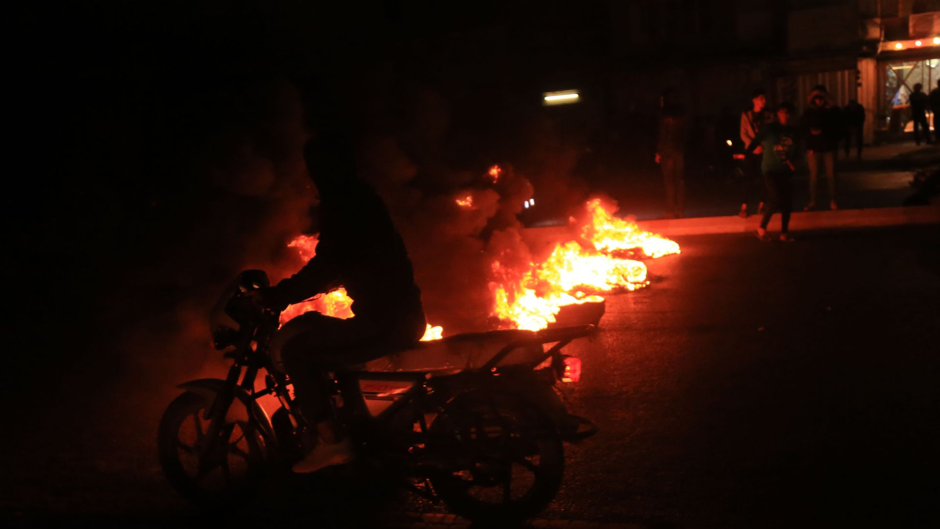 A person riding a bike with a protest in the dark and fire in the background.
