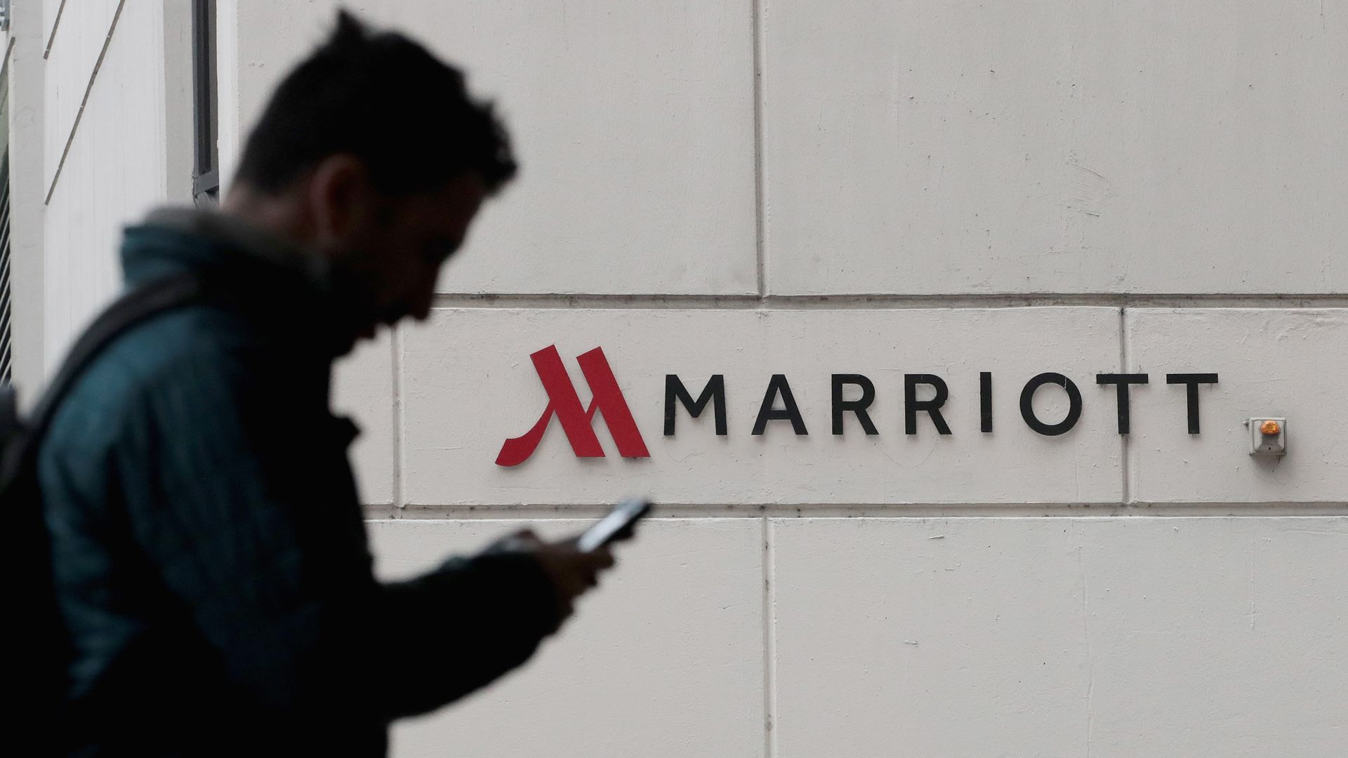 A man walks by the Marriott logo