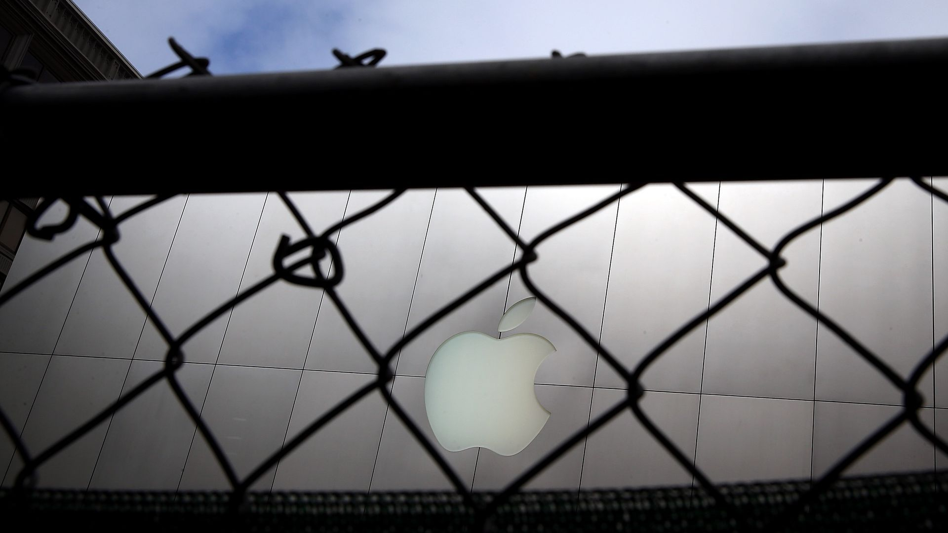 Apple laptop with its log as seen outside through a chain link fence