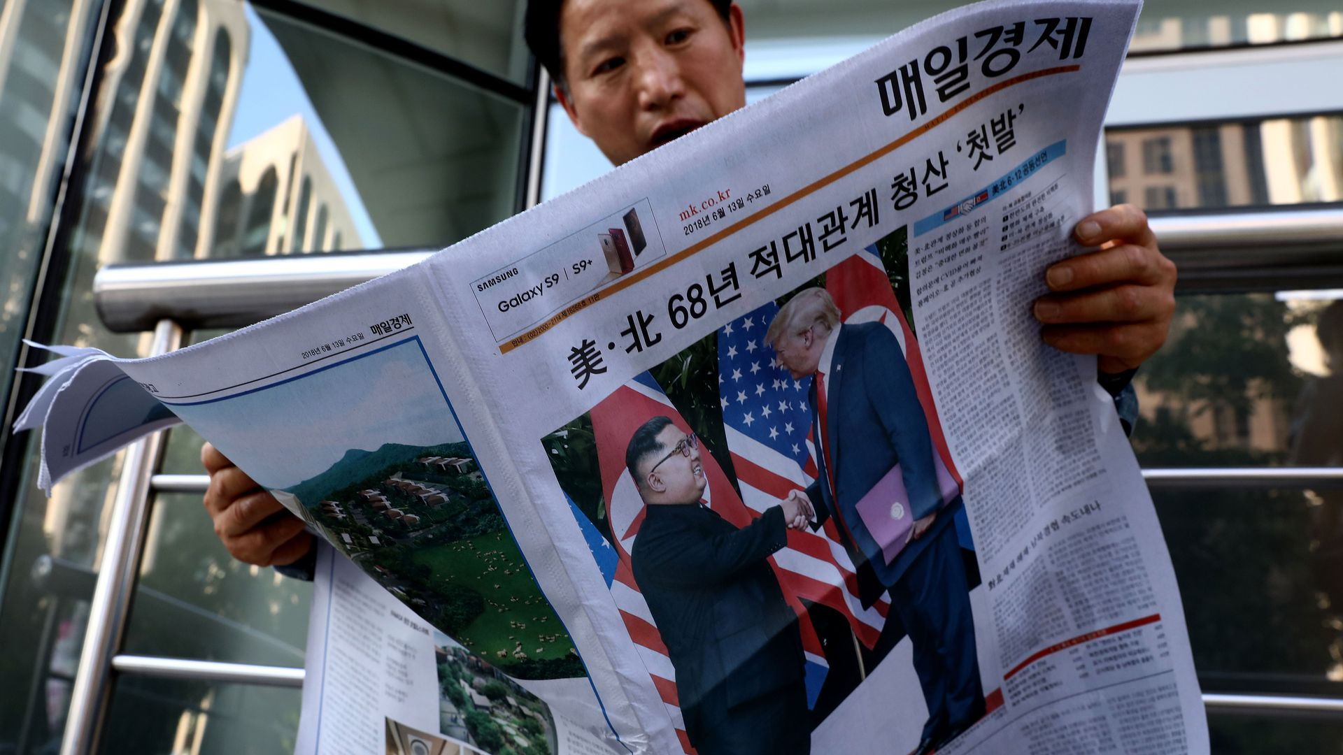 An Asian man reading a newspaper with a photo of Kim Jong-un and Donald Trump shaking hands on the front page