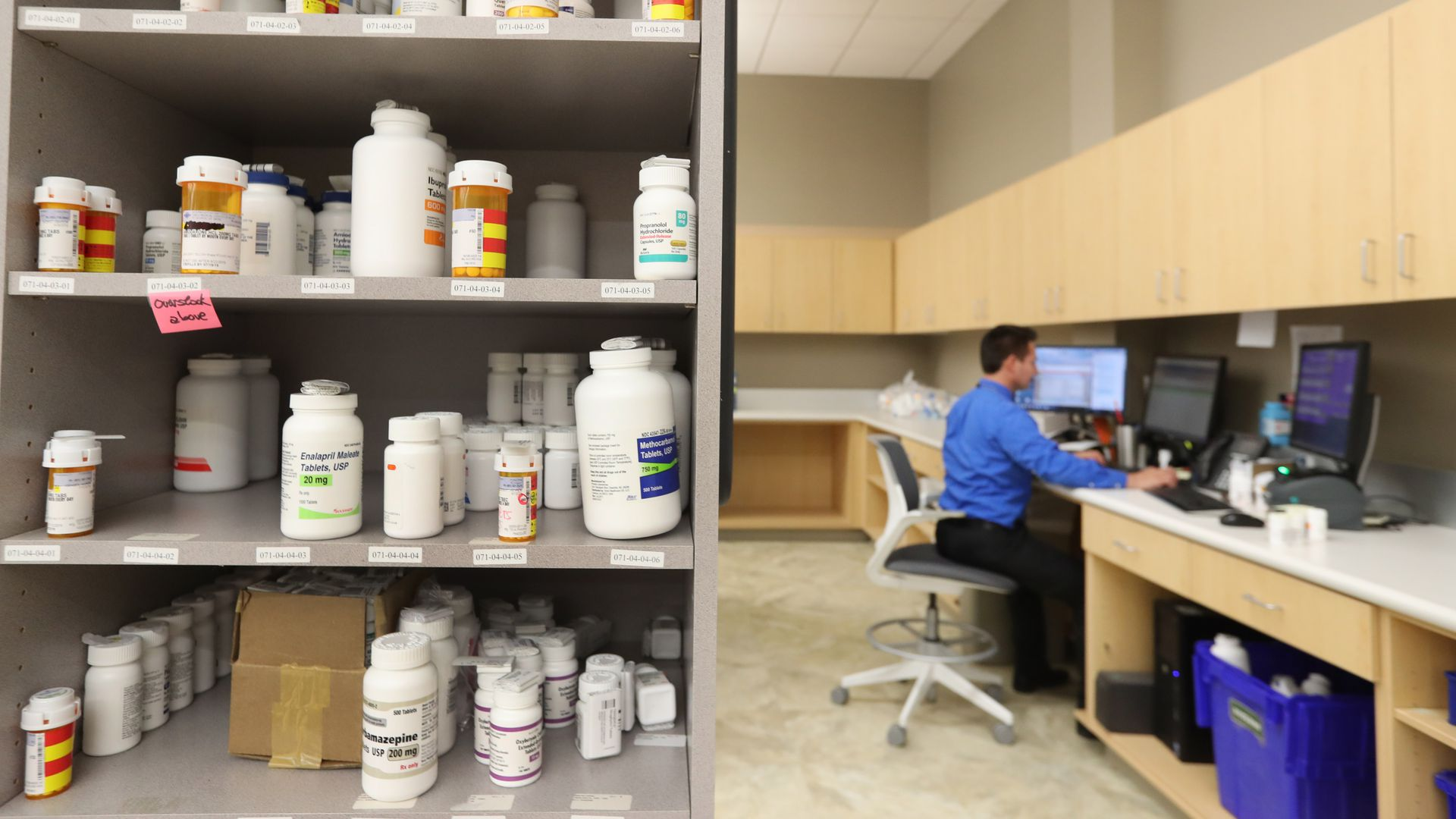 A pharmacy technician works at a desk with drugs sitting on a shelf in the foreground.