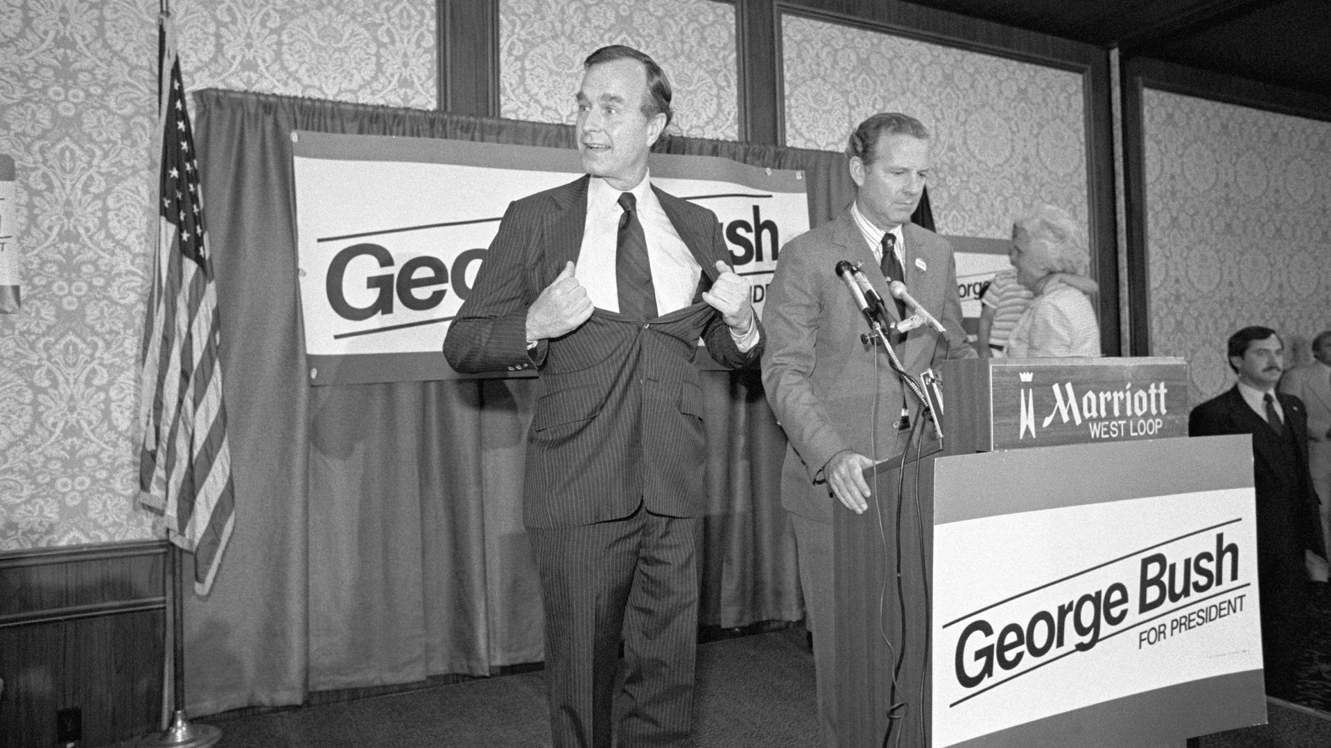 In 1980, Bush campaign manager James Baker stands at the podium while George H.W. Bush makes a joking gesture when told to loosen it up.