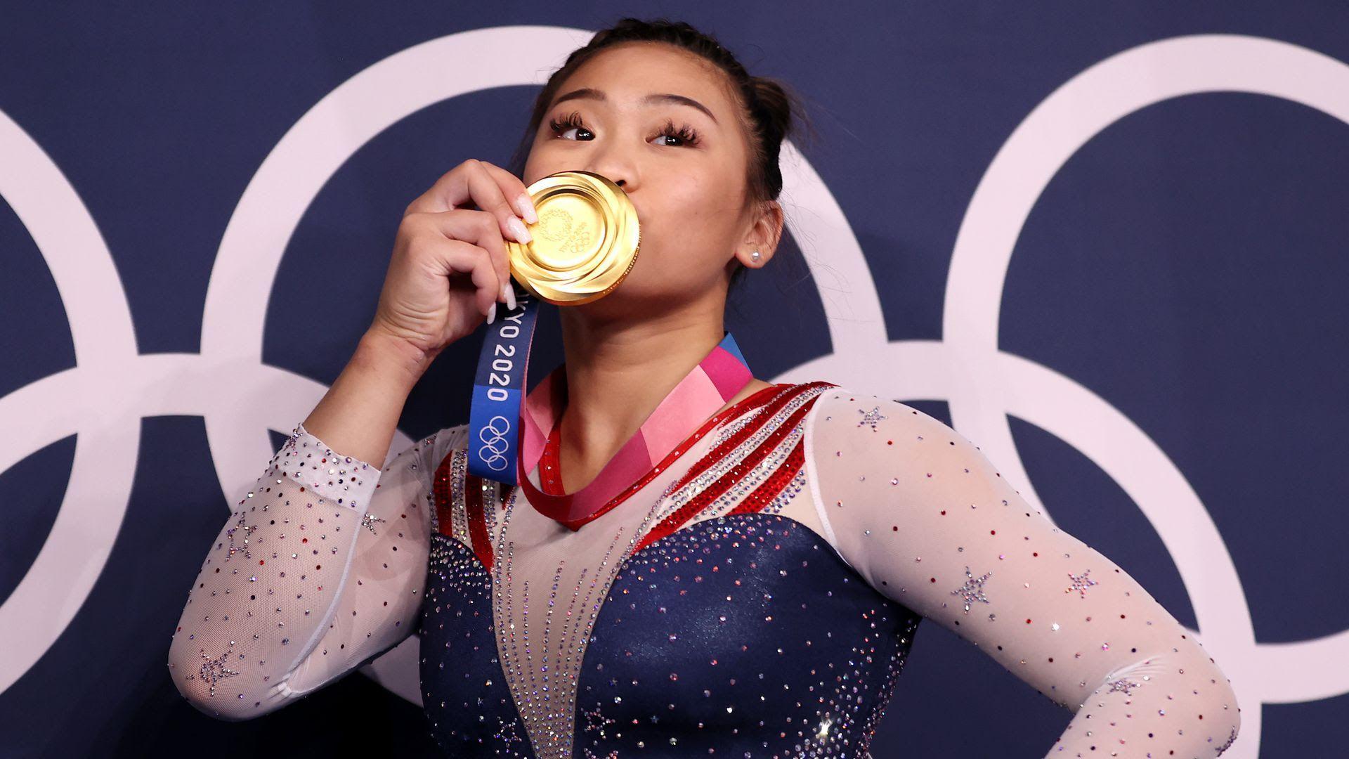 Suni Lee kisses her gold medal in Tokyo.