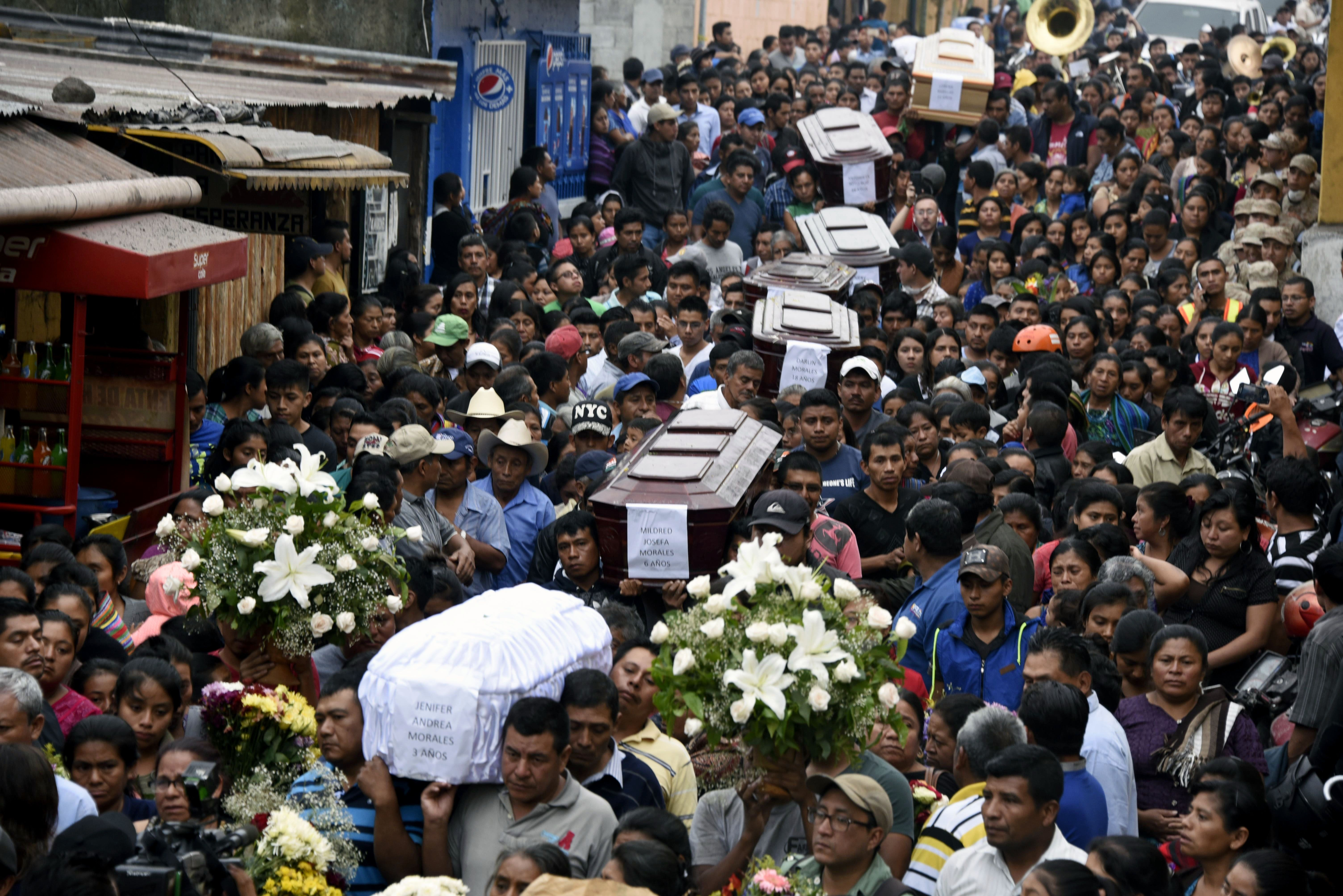 Residents carry the coffins of seven people who died following the eruption of the Fuego volcano.