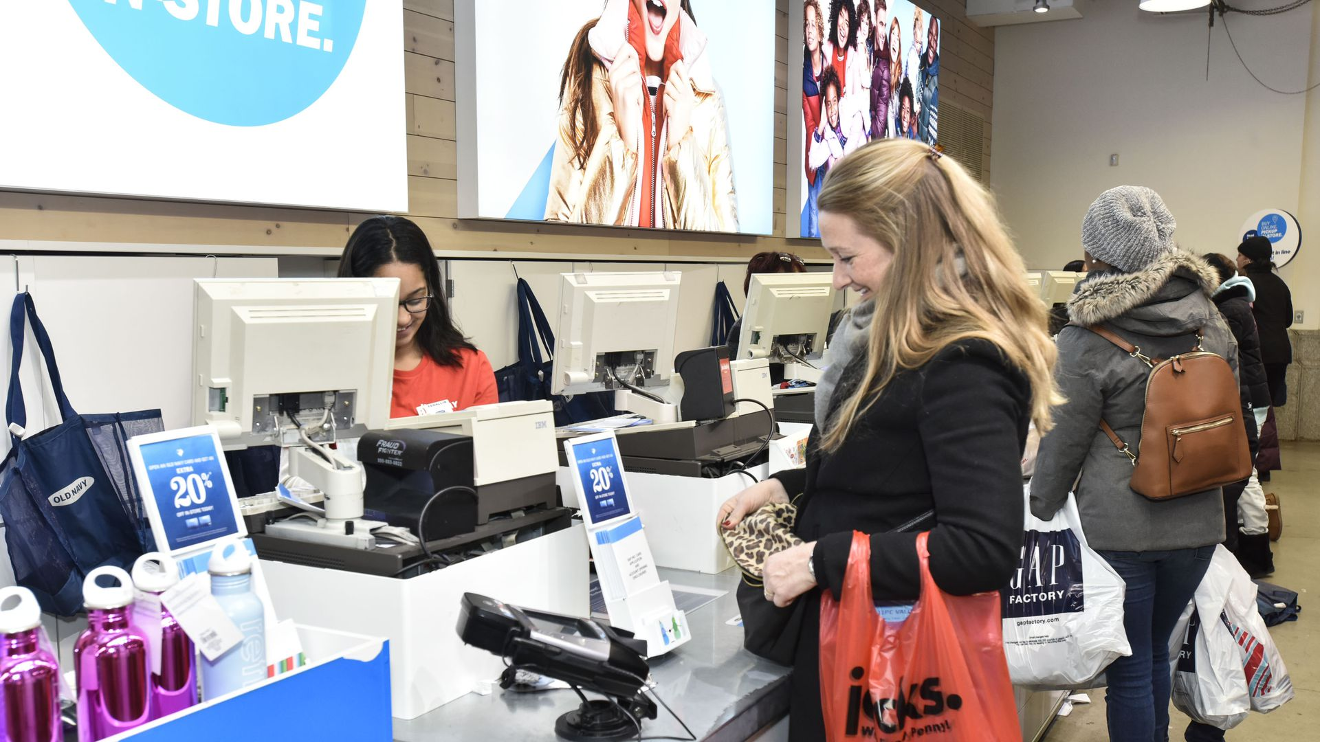 In this image, a woman in a winter coat pays for her items at Old Navy.
